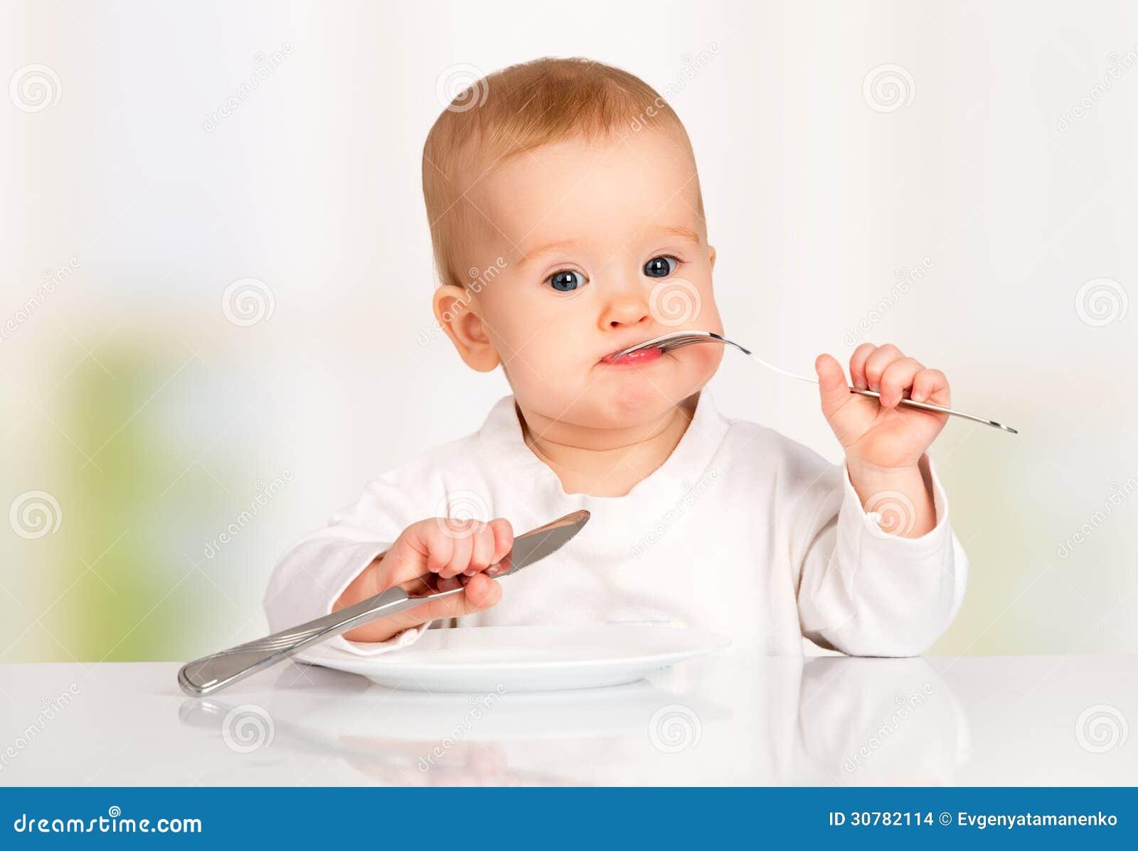 Bebê engraçado com uma faca e uma forquilha que come o alimento