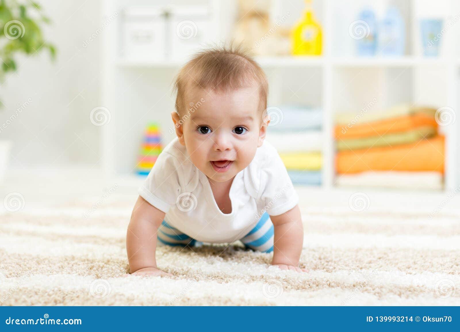 Bebê engraçado de rastejamento dentro em casa