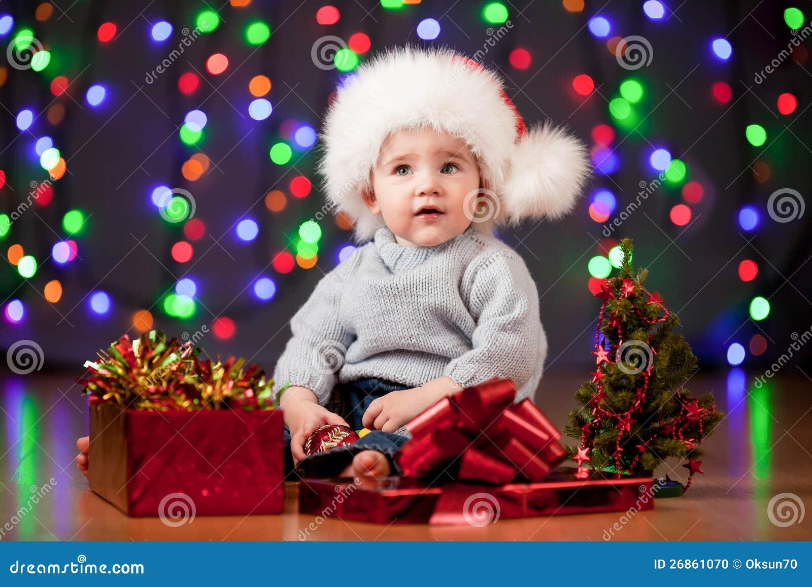 Bebê engraçado no chapéu de Santa no fundo festivo