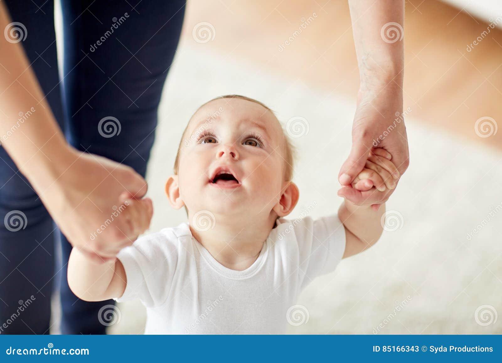 Bebê feliz que aprende andar com ajuda da mãe