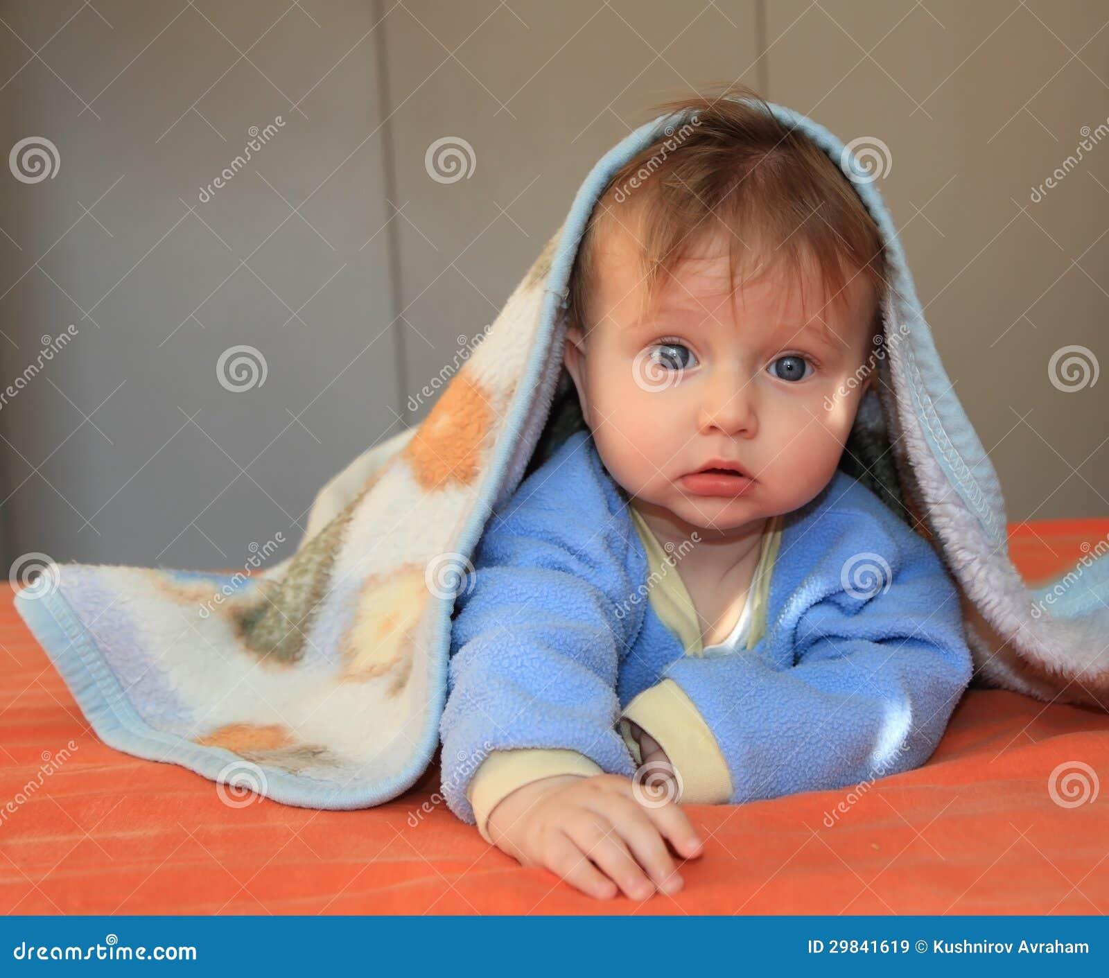 O bebê com os olhos azuis cobertos com uma cobertura