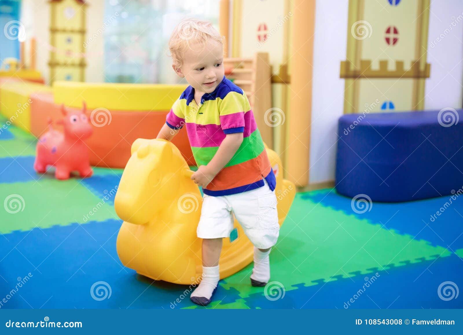 Bebê no balanço na sala do jogo do centro de dia Jogo das crianças