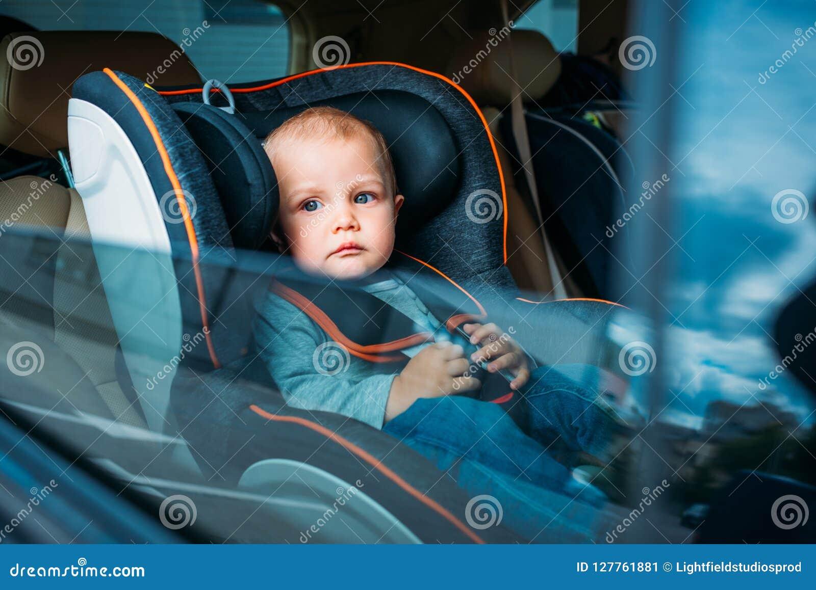 Bebê pequeno bonito que senta-se na criança