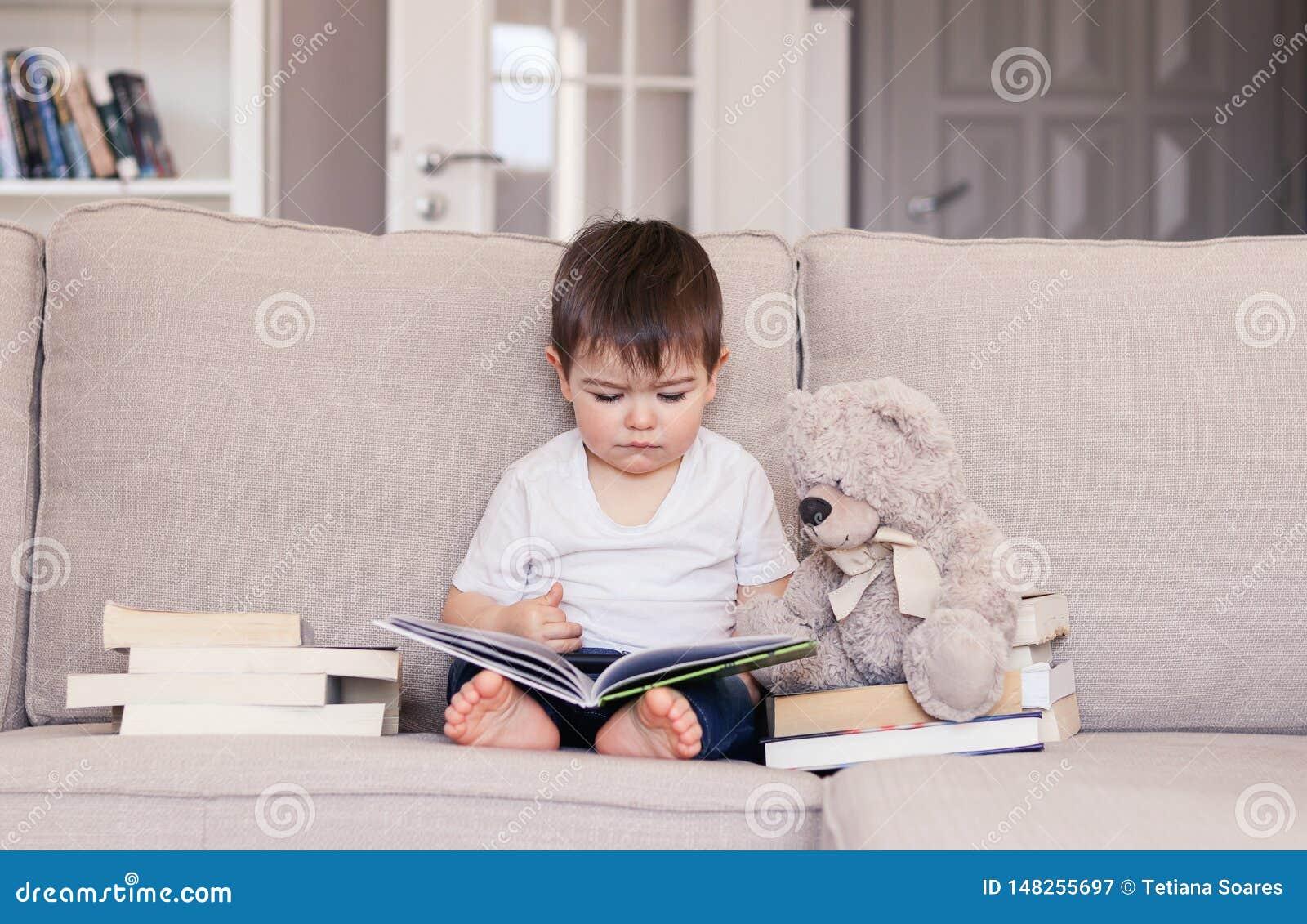 Bebê pequeno inteligente bonito afiado sobre o livro de leitura que senta-se no sofá com o brinquedo do urso de peluche e a pilha