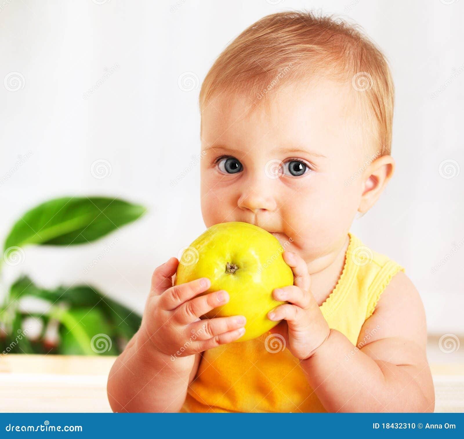 Bebê pequeno que come a maçã