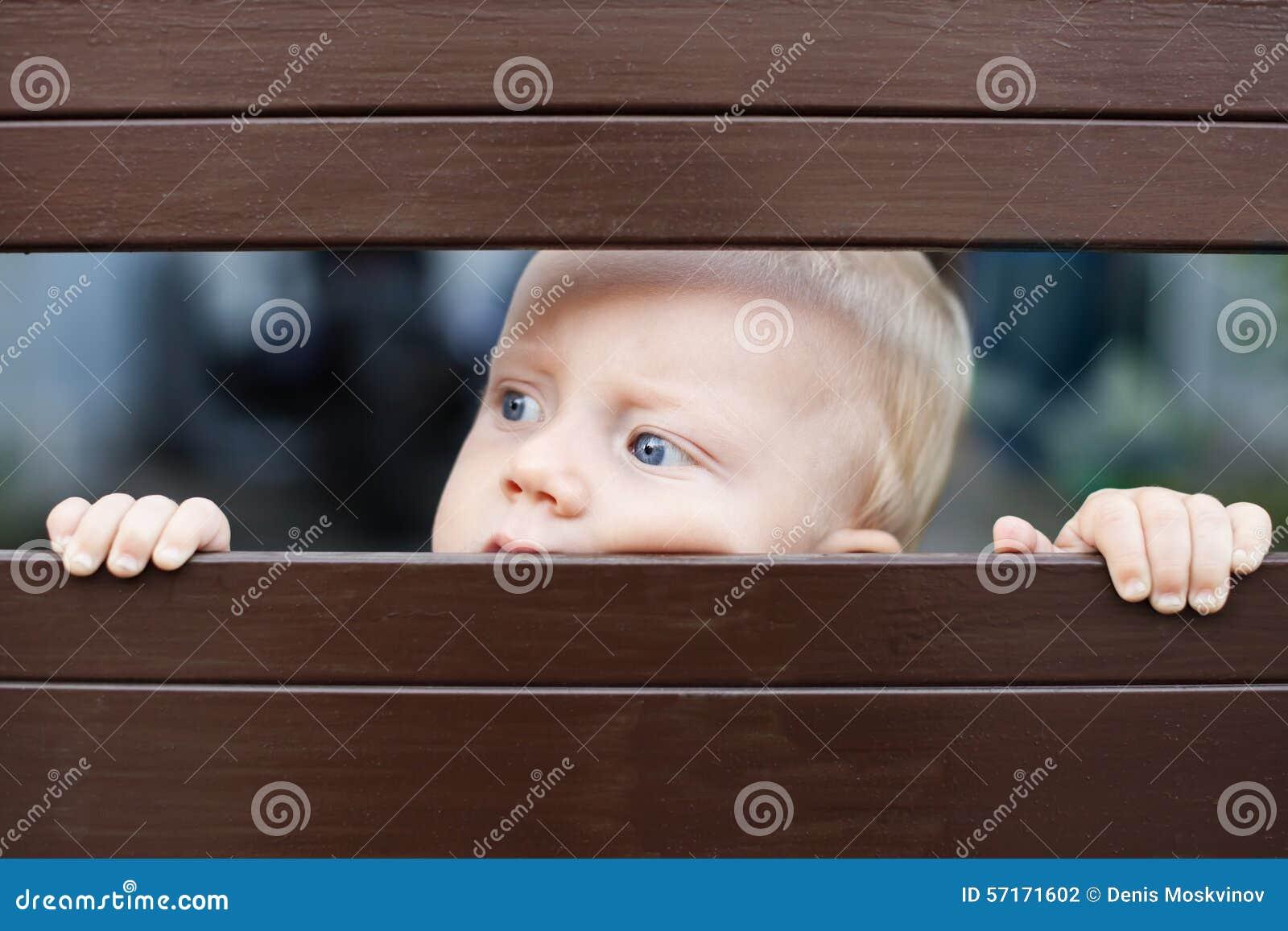 Bebê pequeno que olha para fora através da cerca