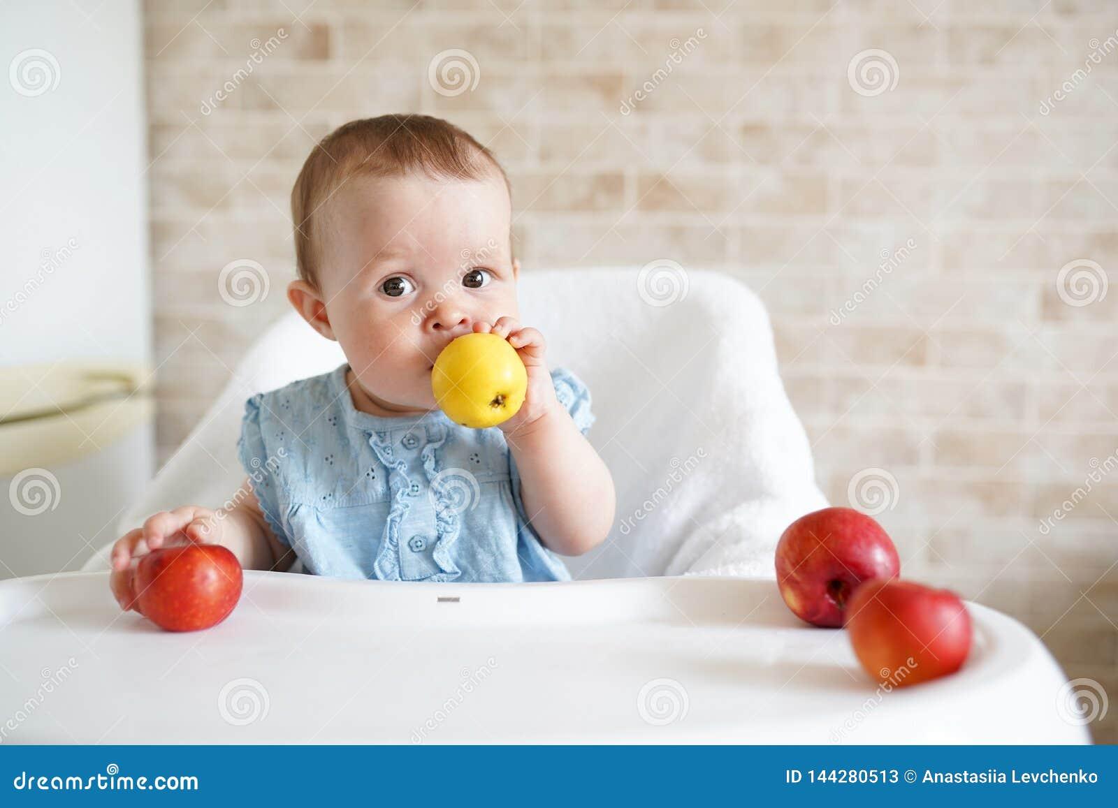 Bebê que come o fruto Menina que morde a maçã amarela que senta-se na cadeira alta branca na cozinha ensolarada Nutrição saudável