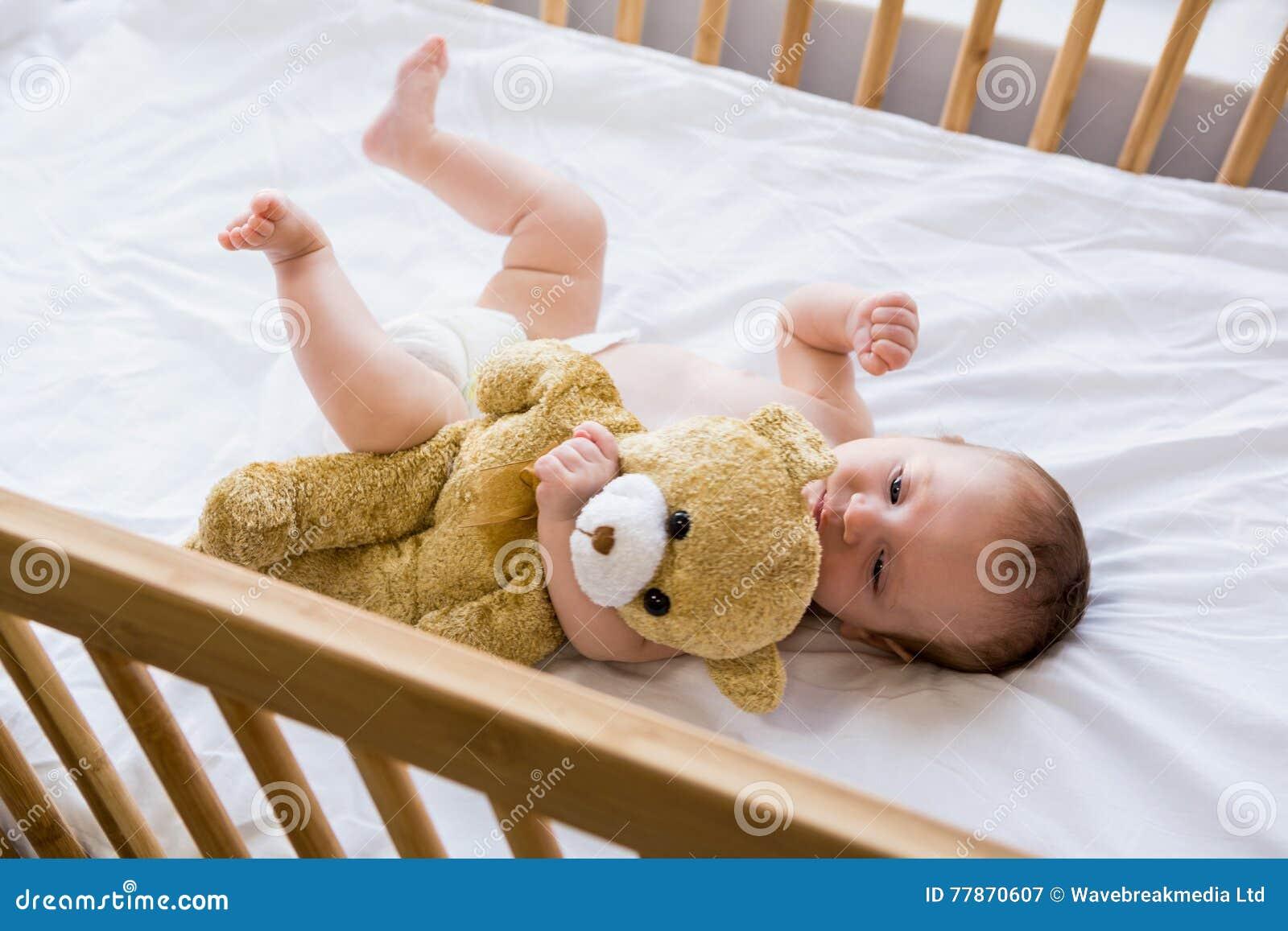 Bebê que encontra-se na cama de bebê