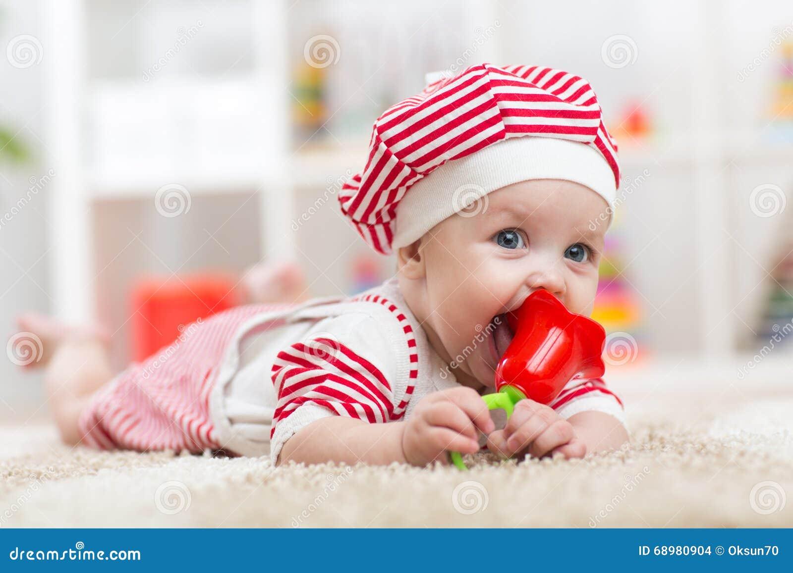 Bebê que guarda um brinquedo e que encontra-se na barriga no berçário