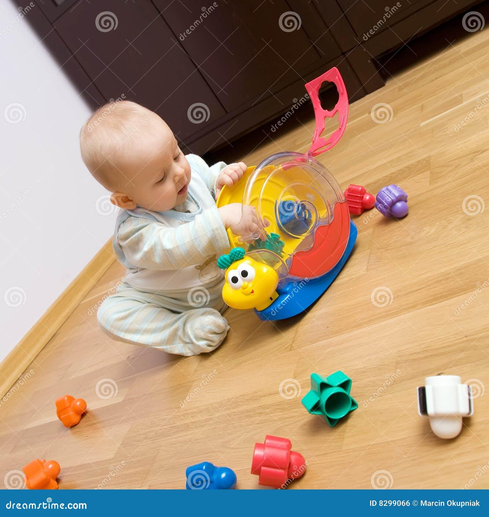 Bebê que joga com brinquedo plástico
