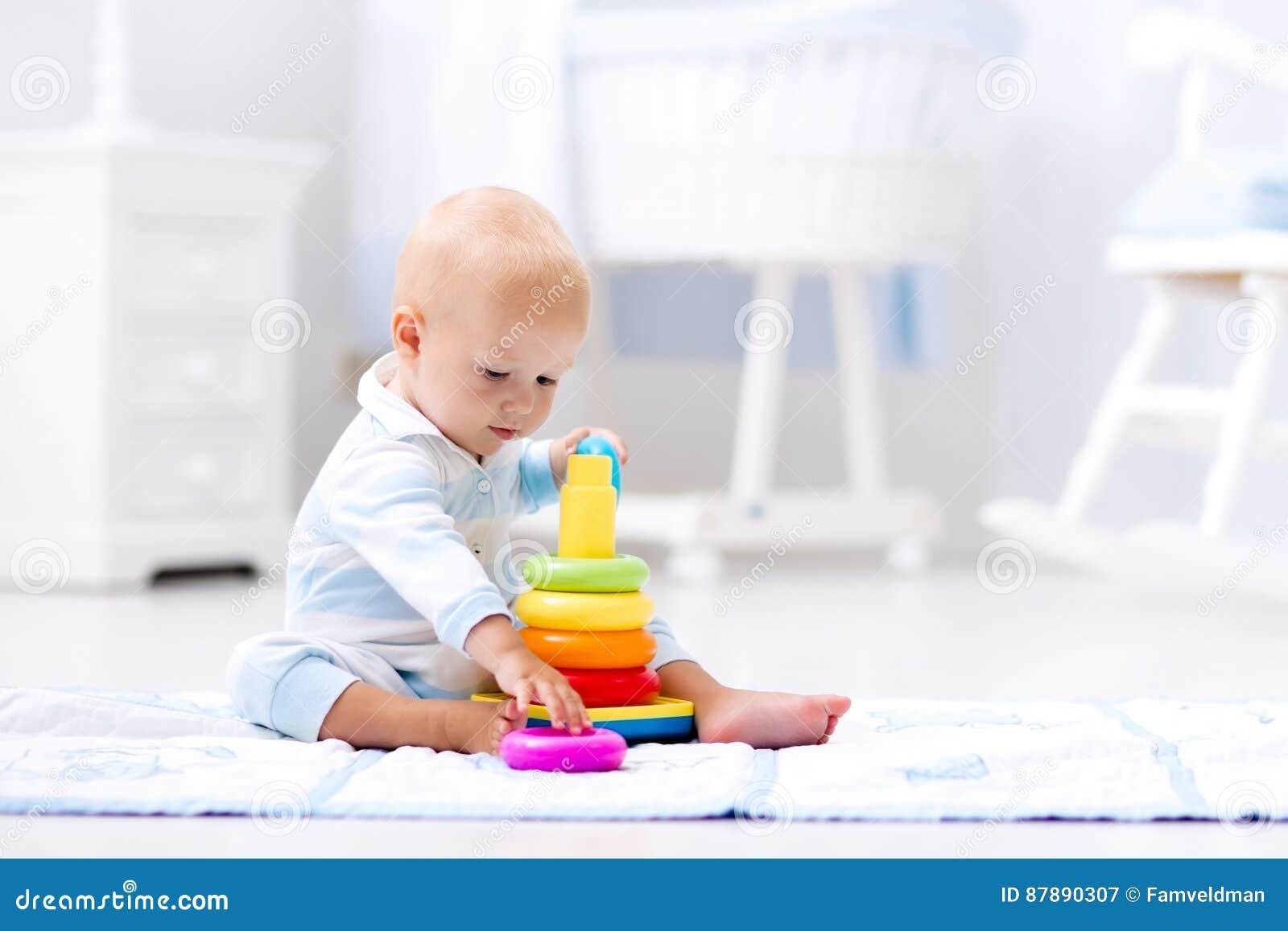 Bebê que joga com pirâmide do brinquedo Jogo das crianças