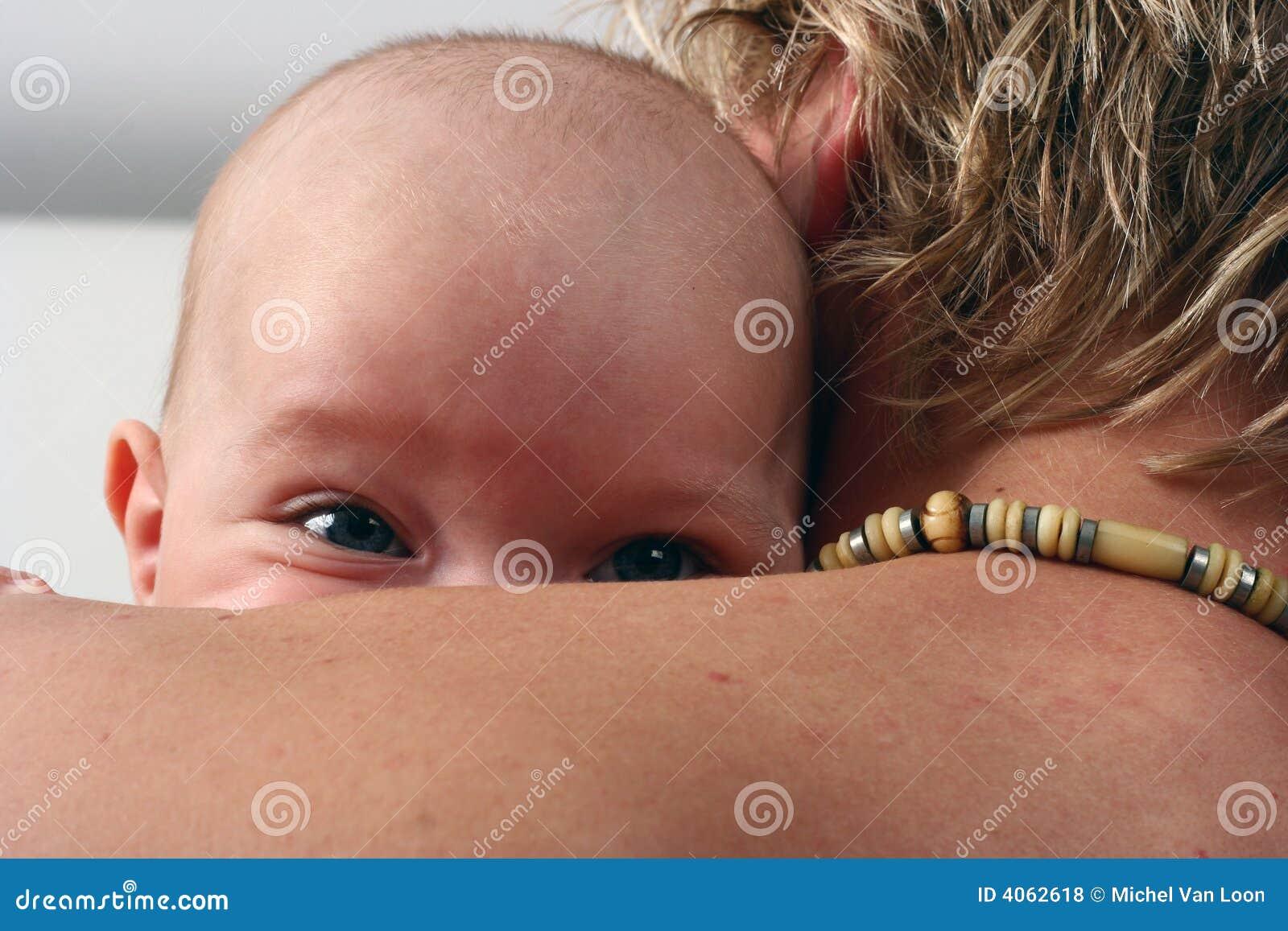 Bebê que presta atenção sobre o ombro