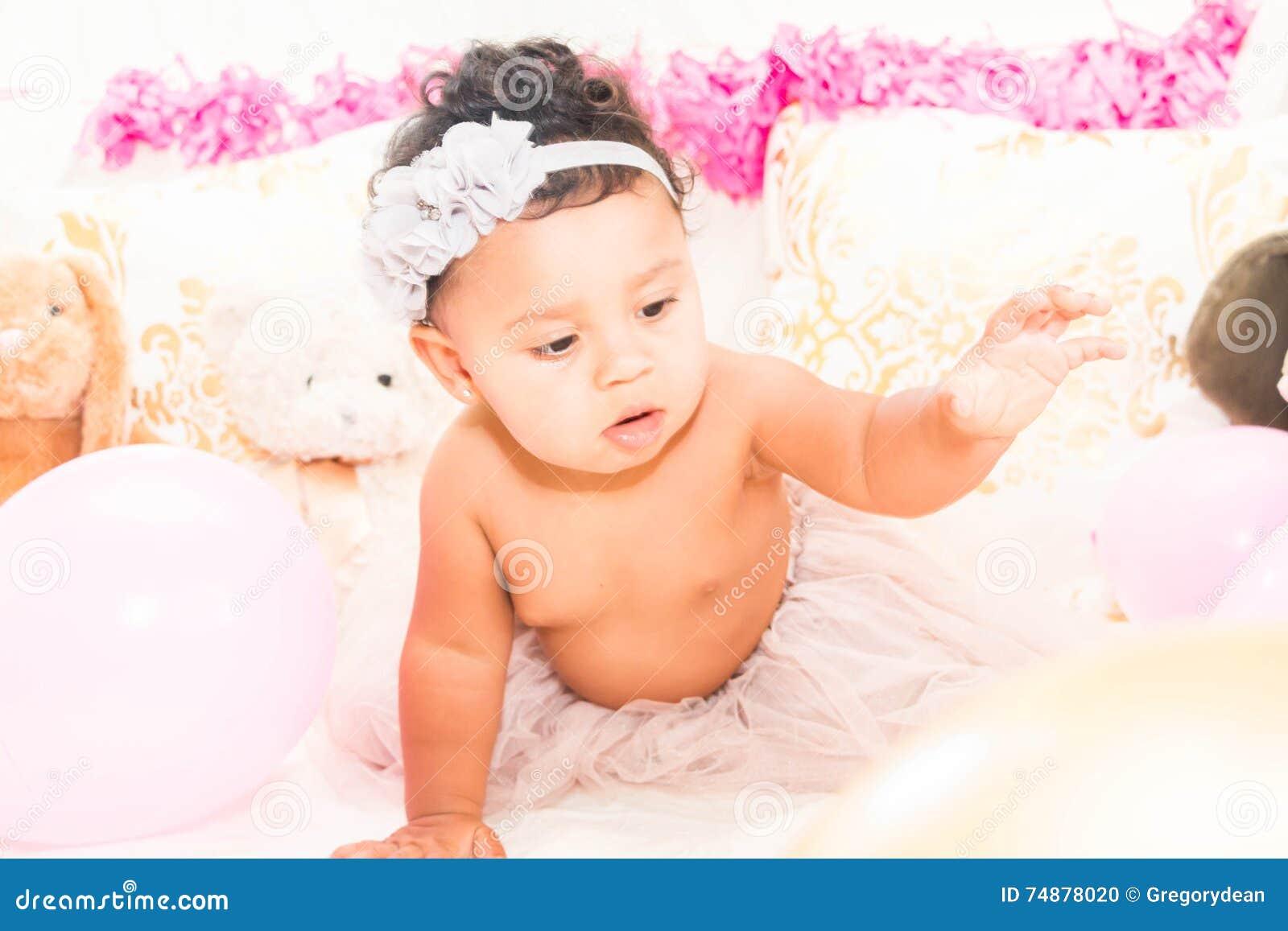 Bebê que senta-se com descansos e balões