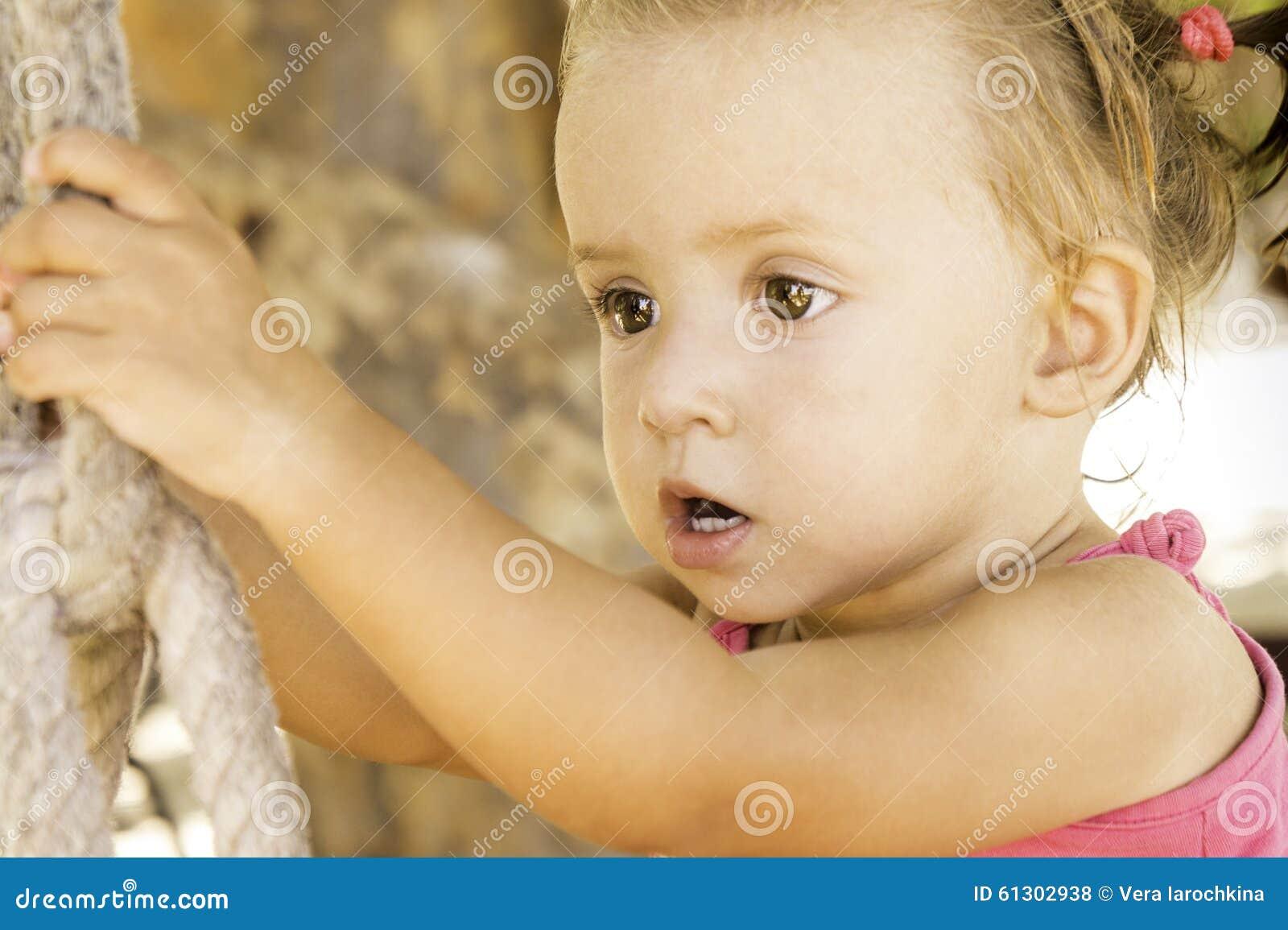 Bebê que senta-se no balanço e que olha fora na distância