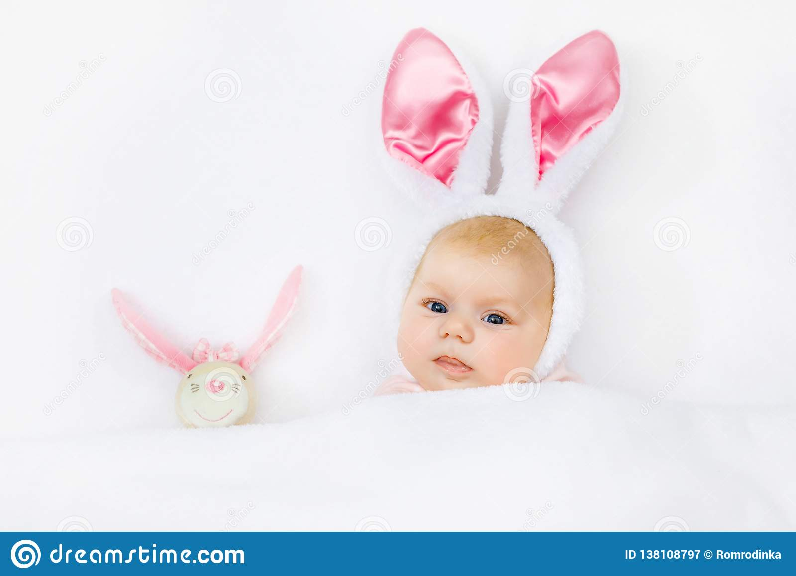 Bebê recém-nascido bonito adorável no traje e nas orelhas do coelhinho da Páscoa Criança bonita que joga com o brinquedo do coelh