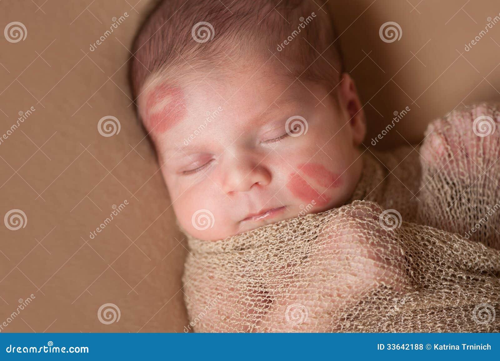 Bebê recém-nascido com beijos do batom na cara