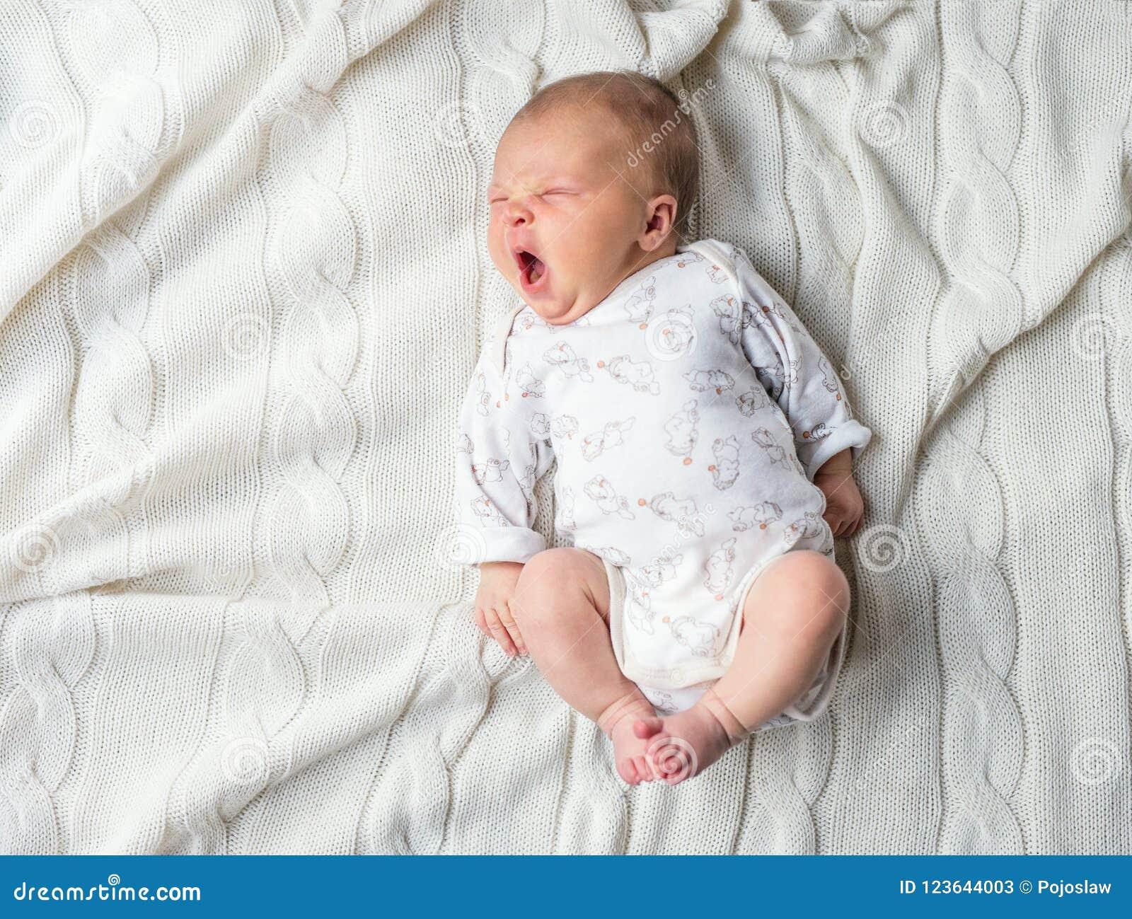 Bebê recém-nascido que encontra-se em uma cobertura branca, bocejando Vista superior