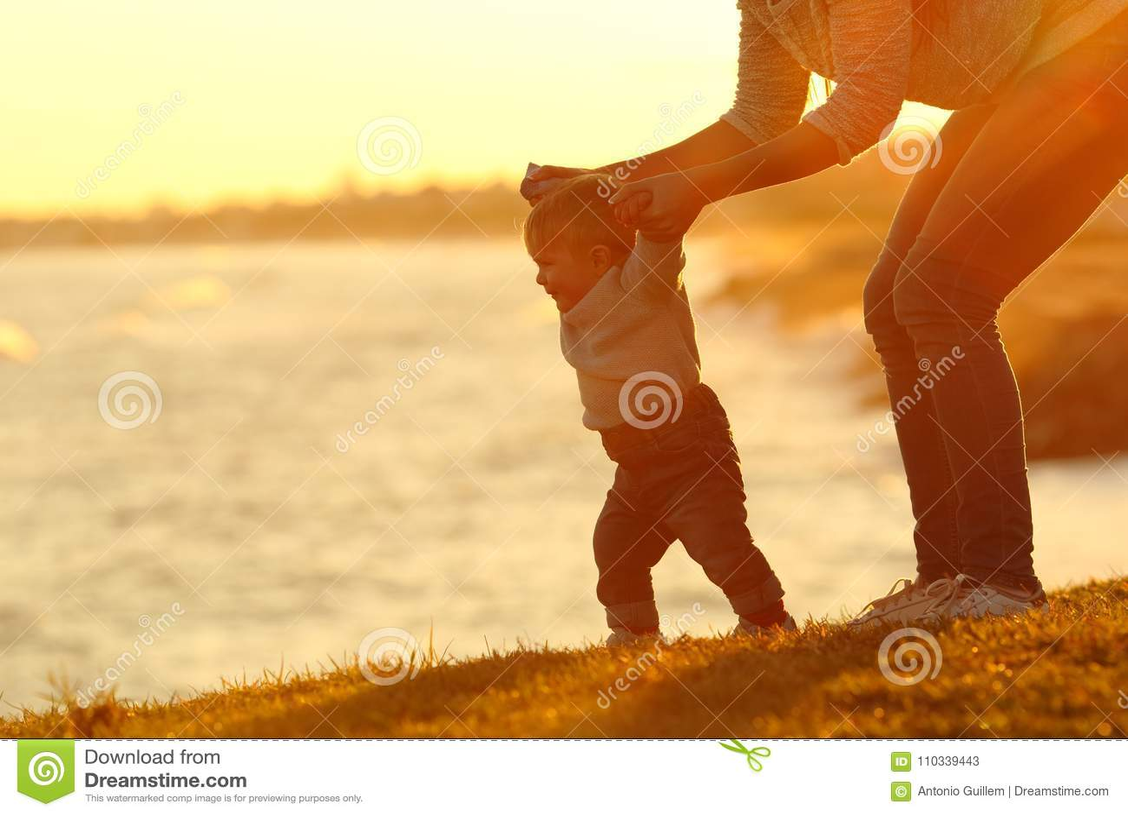 Bebê seguro que aprendem andar e mamã que ajuda o