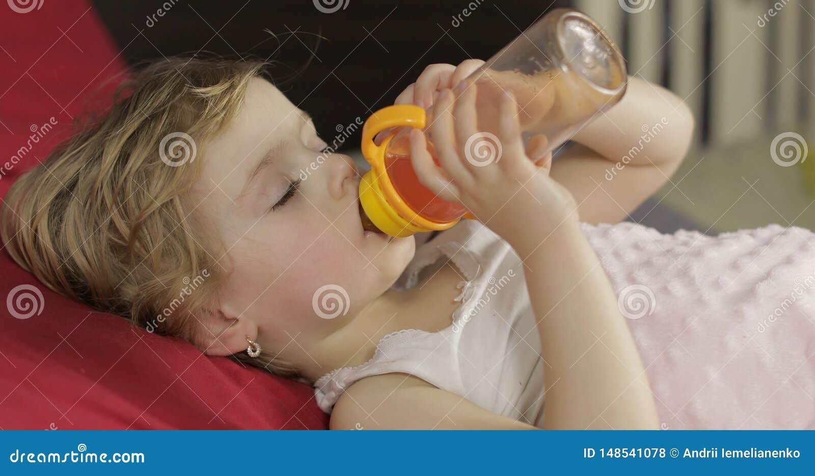 Beb? bonito que dorme na cama acolhedor em casa e no suco bebendo da garrafa