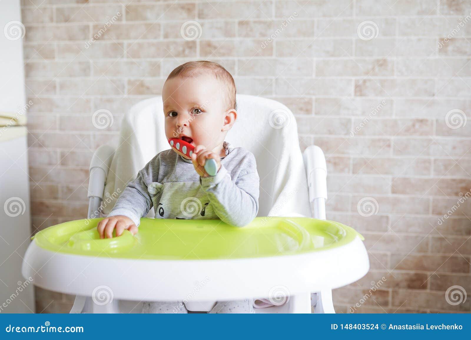 Beb? com a colher na cadeira na sala de jantar, no sorriso e na crian?a feliz Fundo com espa?o da c?pia Inf?ncia feliz