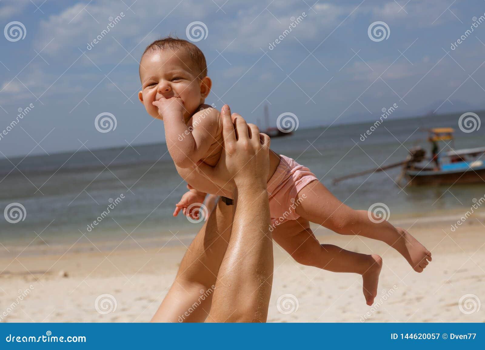 Beb? de sorriso feliz nos bra?os do paizinho Em uma praia tropical O dia ensolarado, pai joga acima a crian?a infantil, posse nas
