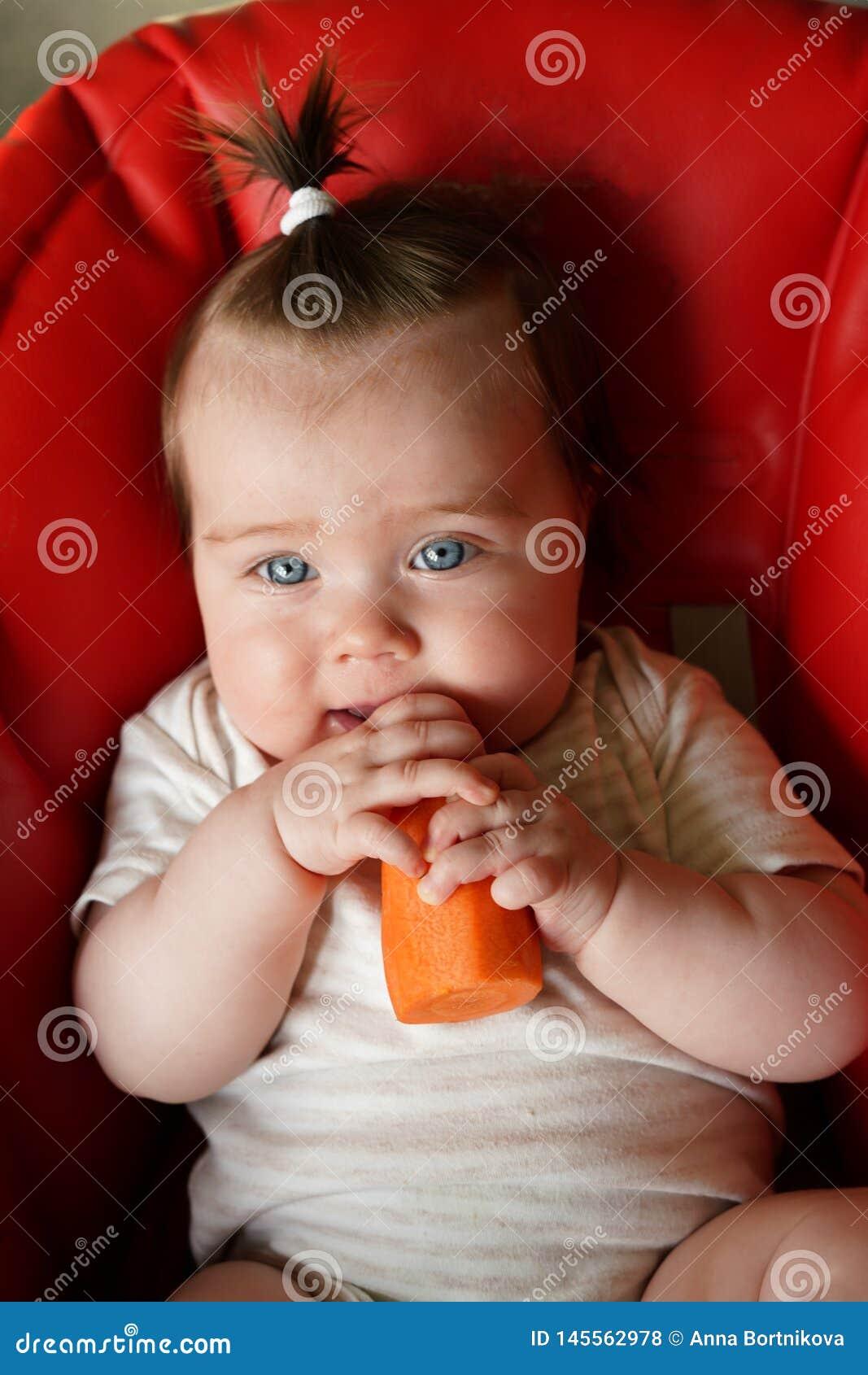 Beb? feliz que intenta su primera comida s?lida vegetal, una zanahoria