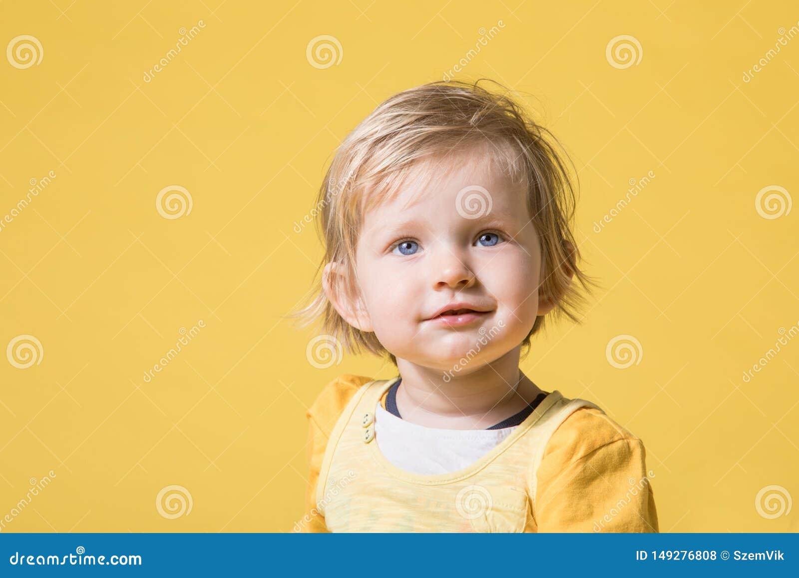 Beb? novo no vestido amarelo no fundo amarelo