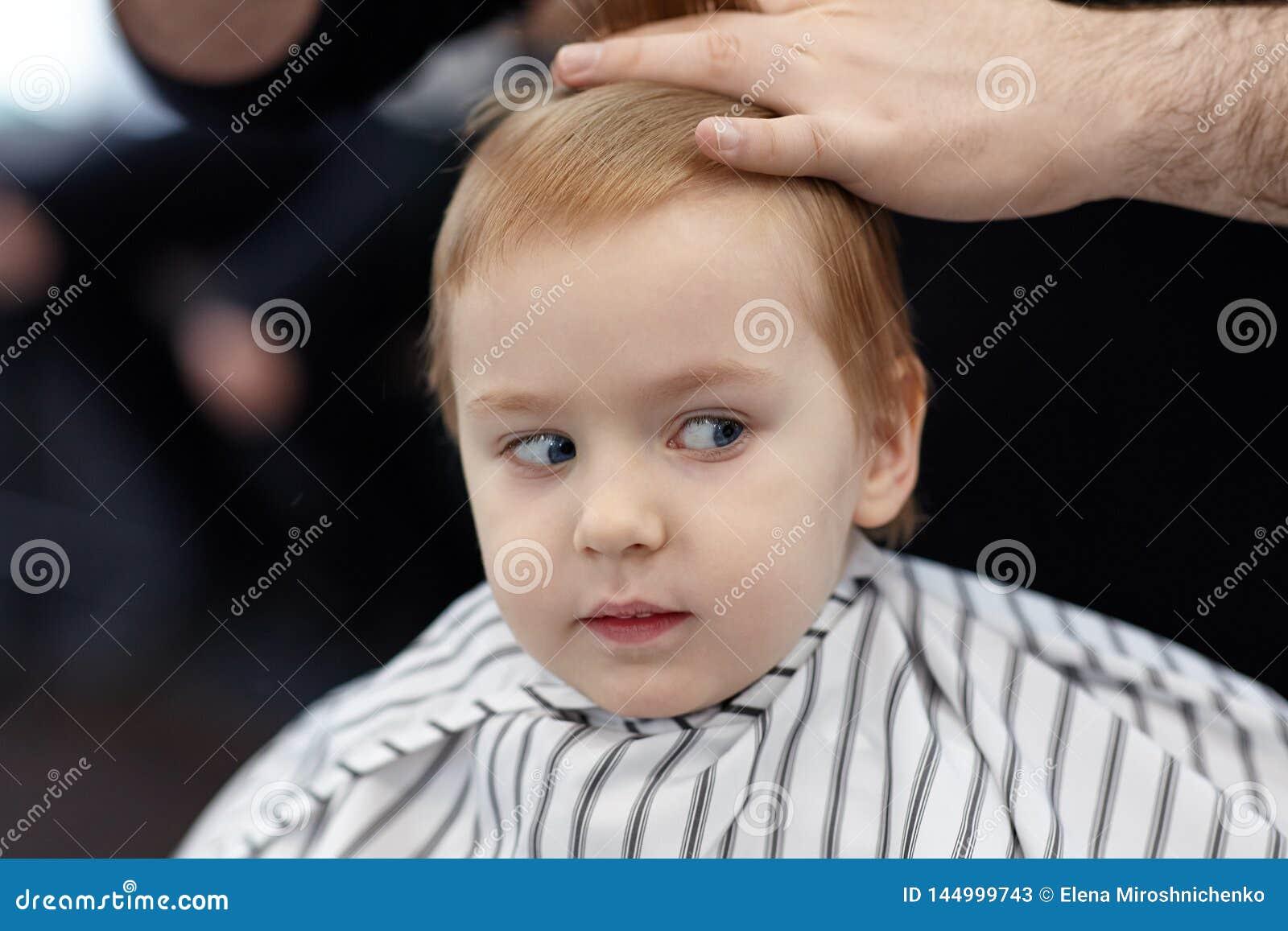 Beb? sonriente rubio lindo con los ojos azules en una peluquer?a de caballeros que tiene corte de pelo del peluquero Manos del es