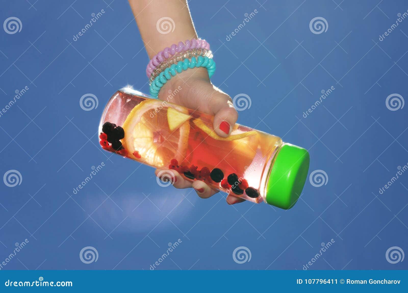 Beba con el limón y las bayas en la botella