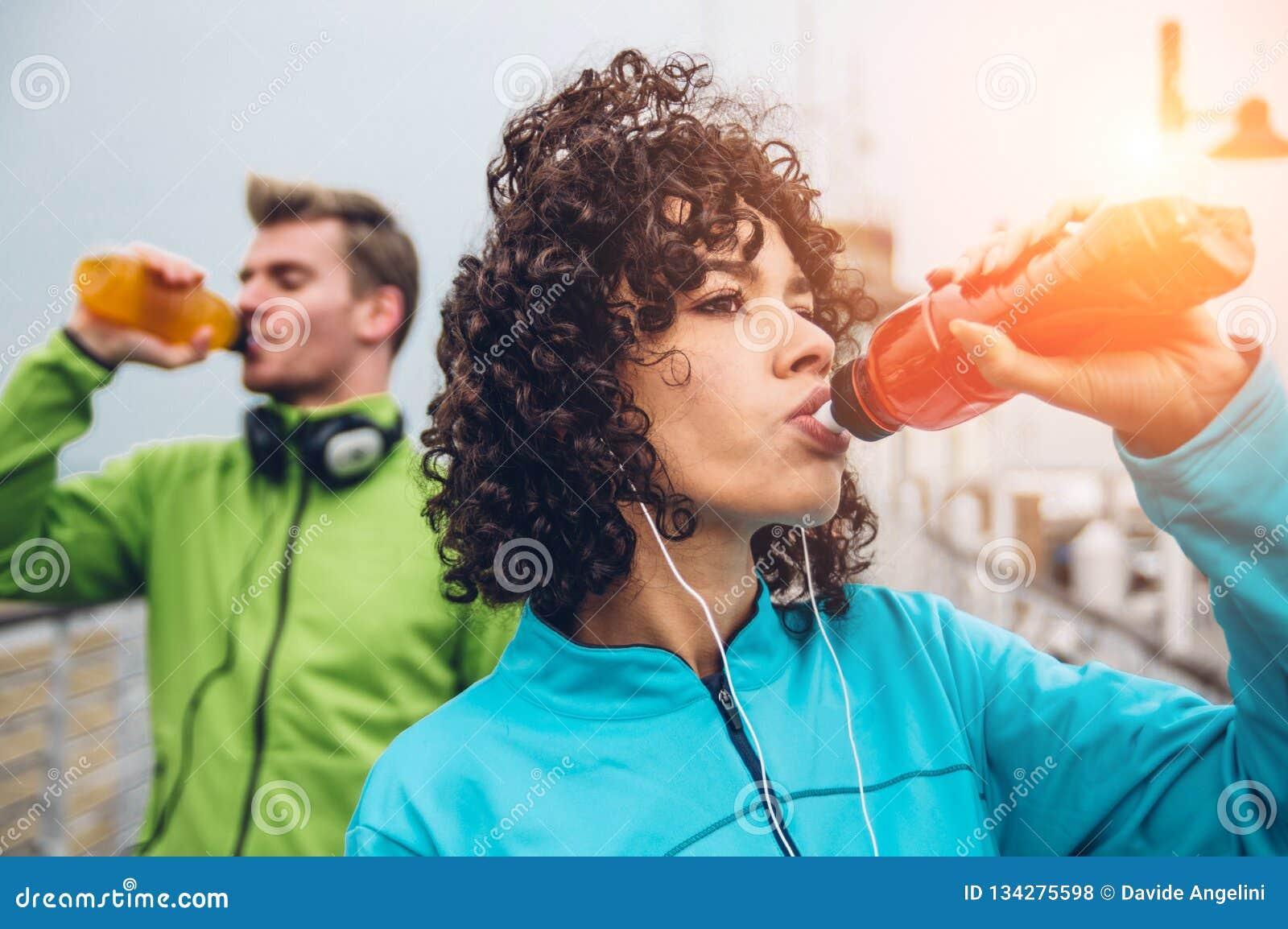 Bebida bebendo da energia do homem e da mulher da garrafa após o exercício do esporte da aptidão