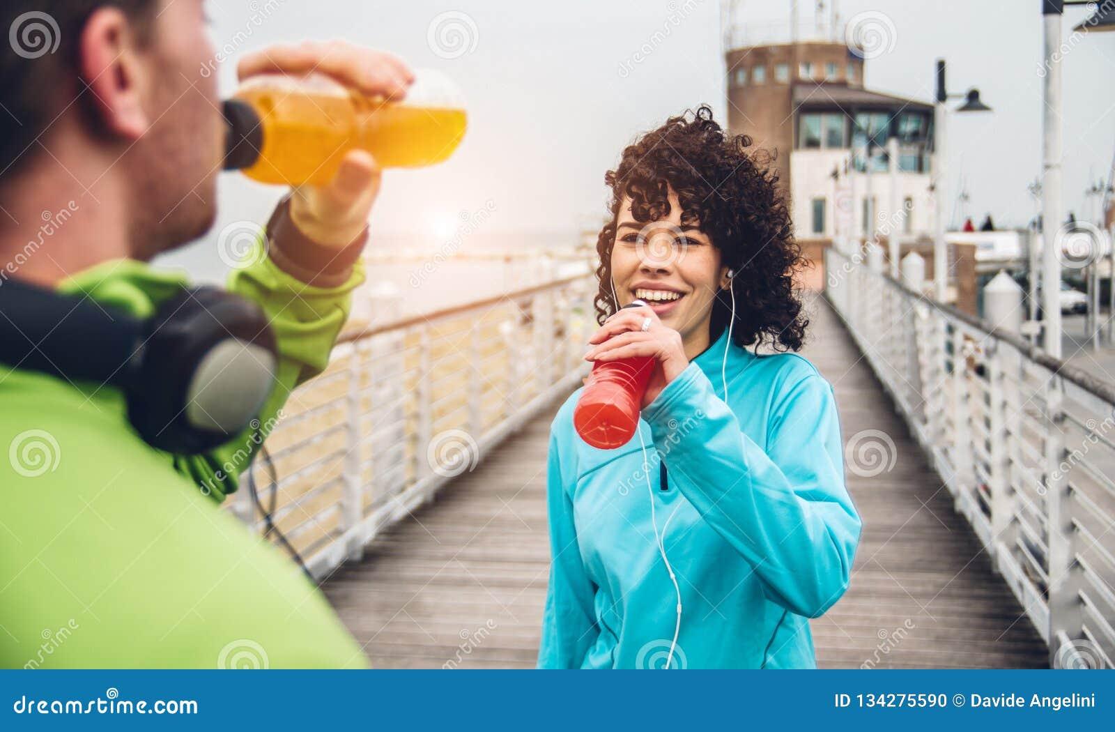 Bebida de consumición de la energía del hombre y de la mujer de la botella después del ejercicio del deporte de la aptitud
