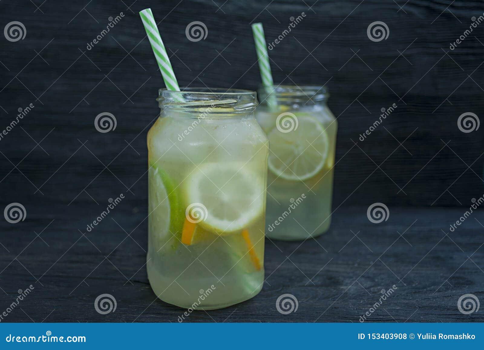 Bebida de restauración del verano de los agrios Bebida de la cal, limón, naranja Fondo de madera oscuro