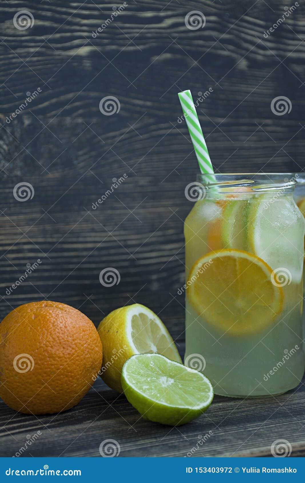 Bebida de restauración del verano de los agrios Bebida de la cal, limón, naranja Fondo de madera oscuro Espacio para el texto