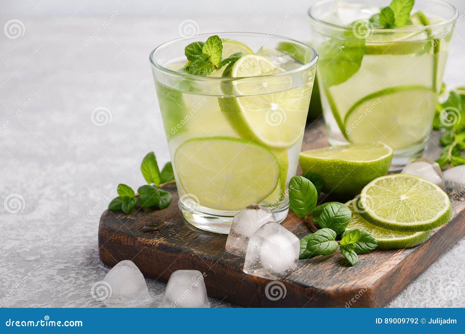 Bebida de restauración fría del verano con la cal y la menta en un vidrio en un fondo concreto o de piedra gris