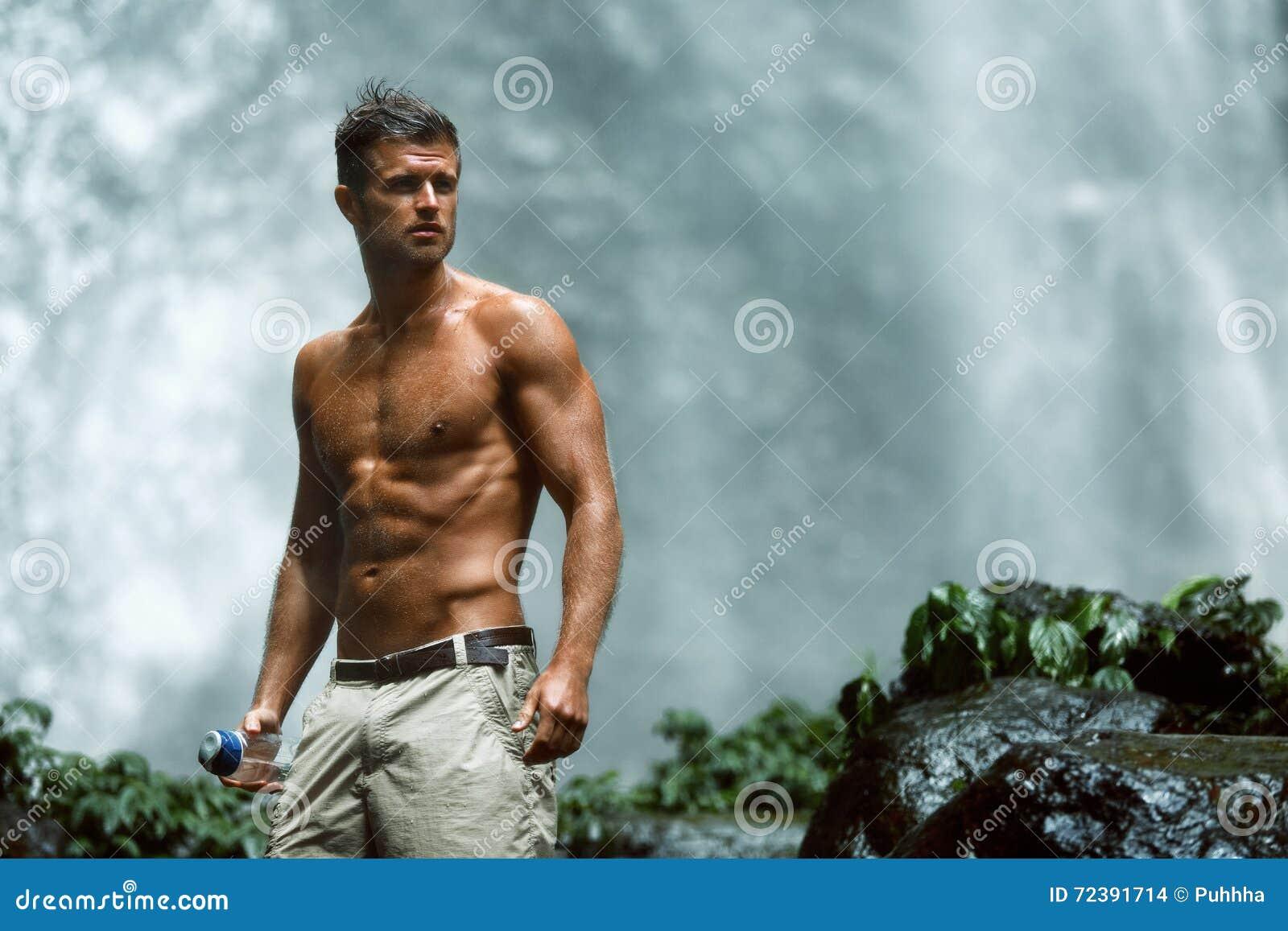 Bebida del agua Hombre sano con el cuerpo atractivo cerca de la cascada salud