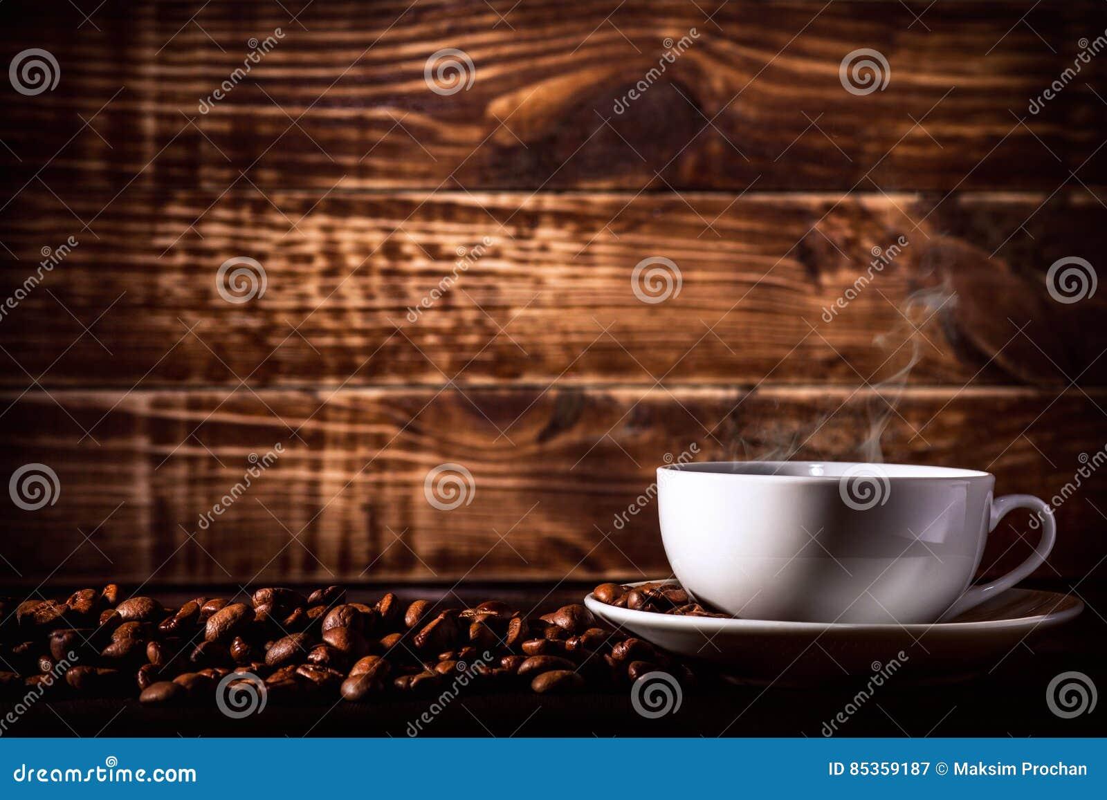 Bebida del café del fondo en una taza con los granos de café en textura de madera