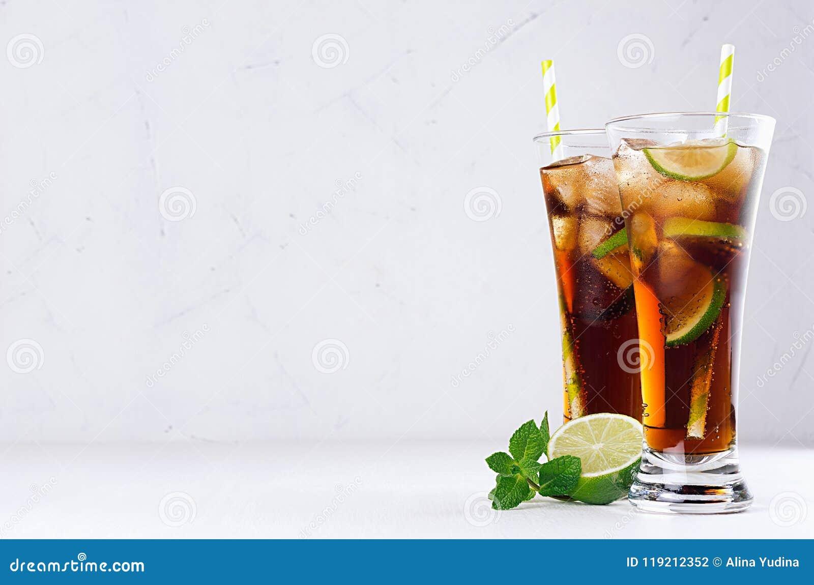 Bebida fría fresca del verano de la cola, hielo, cal, menta de la hoja en el fondo blanco de la luz suave, espacio de la copia