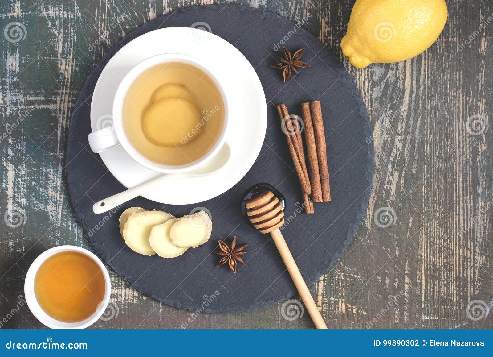 Bebida natural de impulso da vitamina da imunidade quente do gengibre com limão, mel e canela e ingredientes
