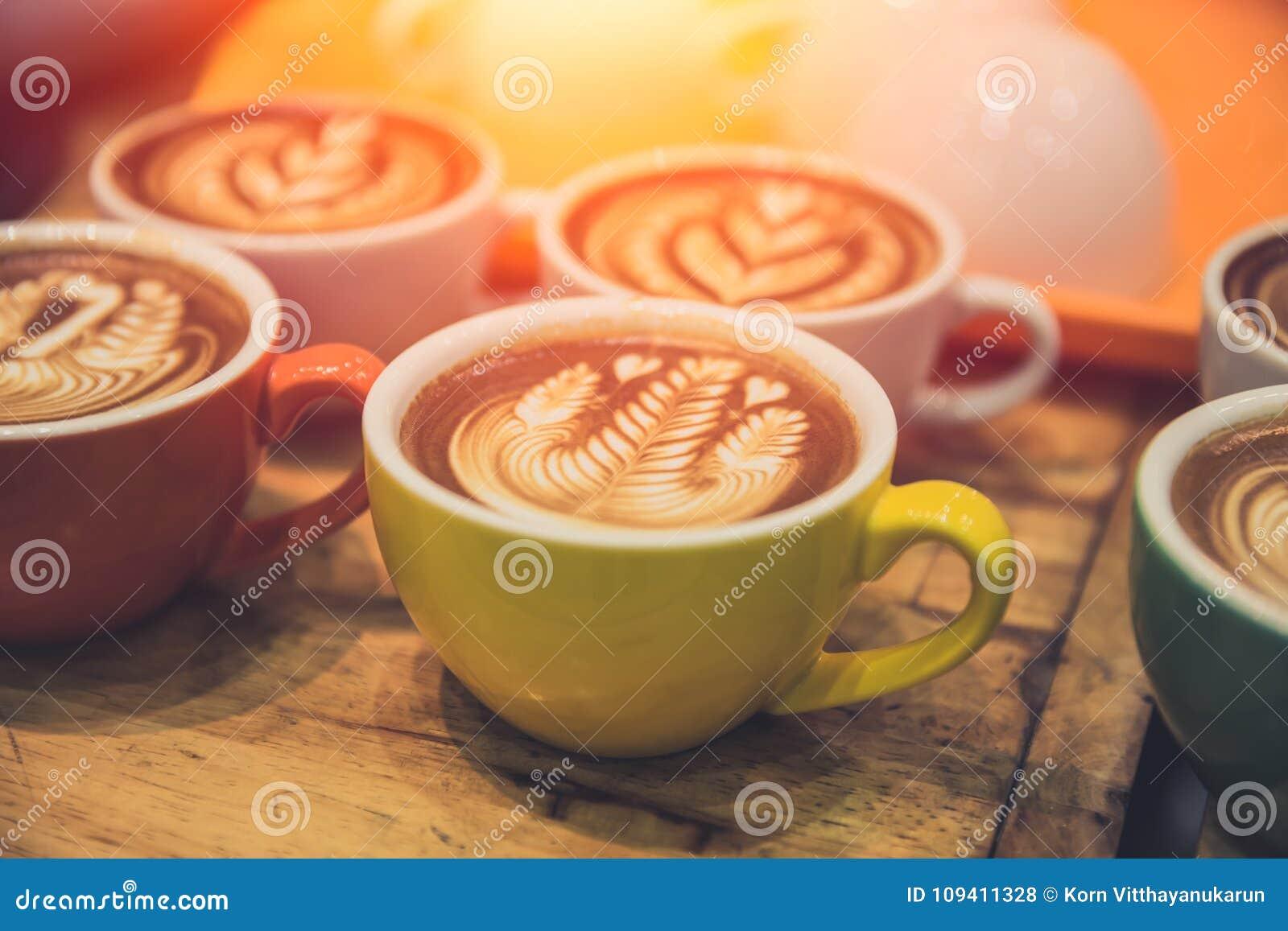 A bebida quente popular da arte do latte do café serviu na tabela de madeira