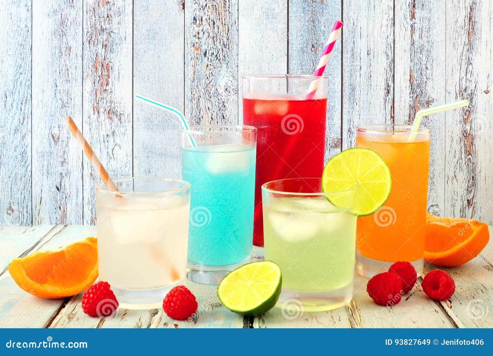 Bebidas coloridas frescas do verão contra a madeira rústica