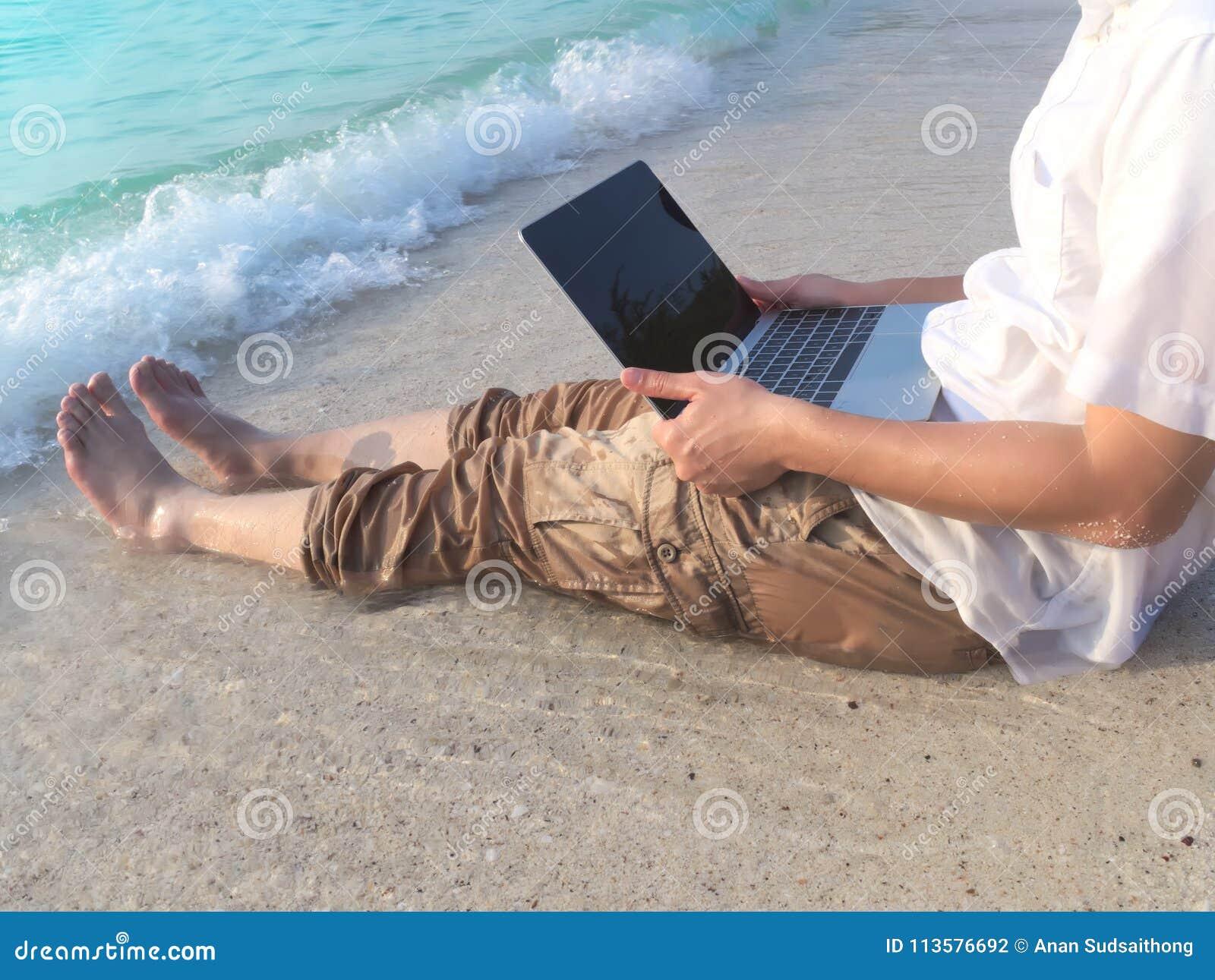 Bebouwd beeld van de ontspannen jonge Aziatische mens met laptop zitting op zand van tropisch strand in vakantiesdag