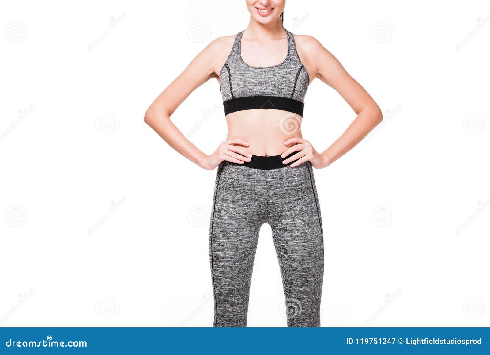 Bebouwd schot die van glimlachende sportvrouw zich met handen op taille bevinden