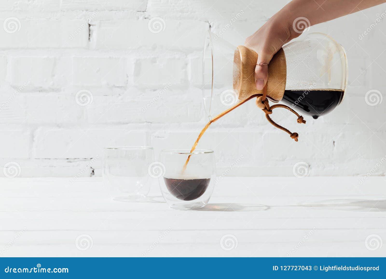 Bebouwd schot die van vrouw alternatieve koffie van chemex gieten in glasmok