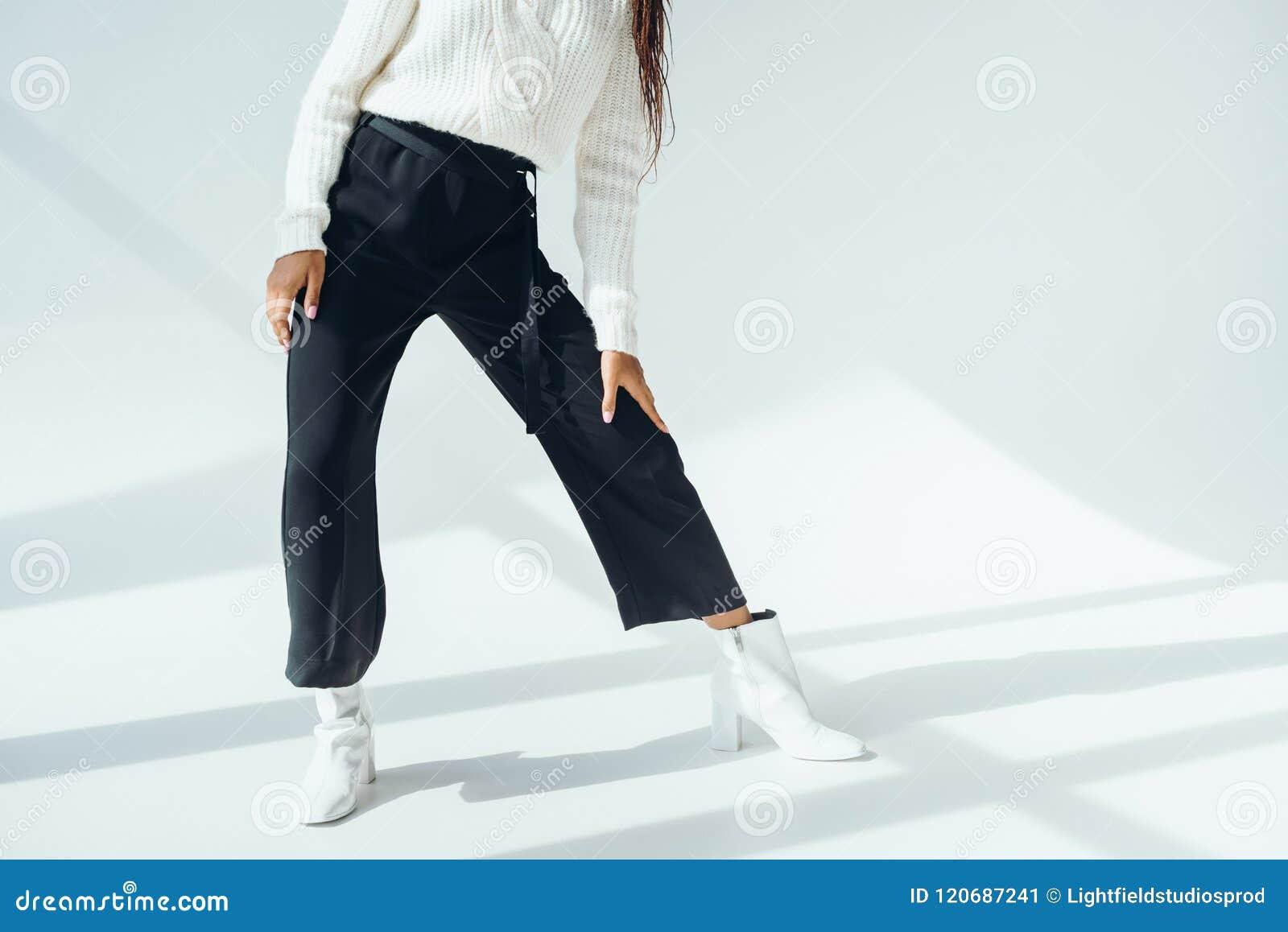 Bebouwd schot van meisje in in zwarte broek en het gebreide sweater stellen