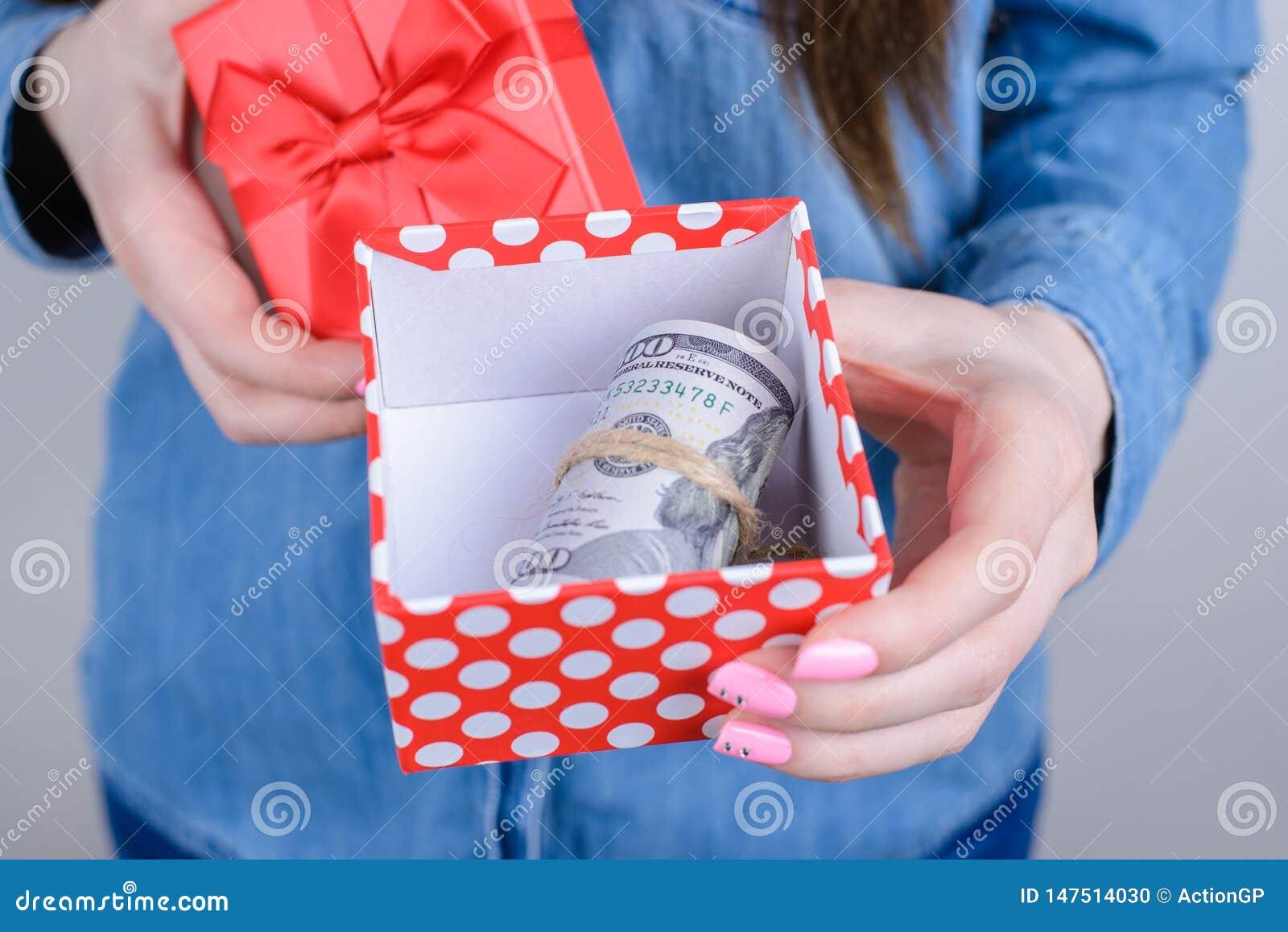 Bebouwde close-upfoto van opgewekte gelukkige zekere bedrijfsonderneemster die pakket met stapelstapel tonen van geldholding in h
