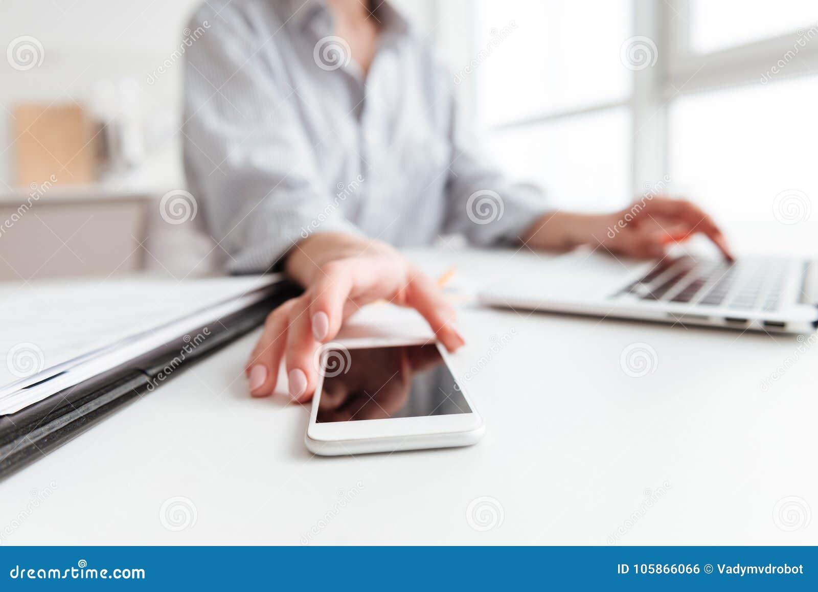 Bebouwde foto van vrouw in smartphone van de overhemdsholding terwijl het zitten