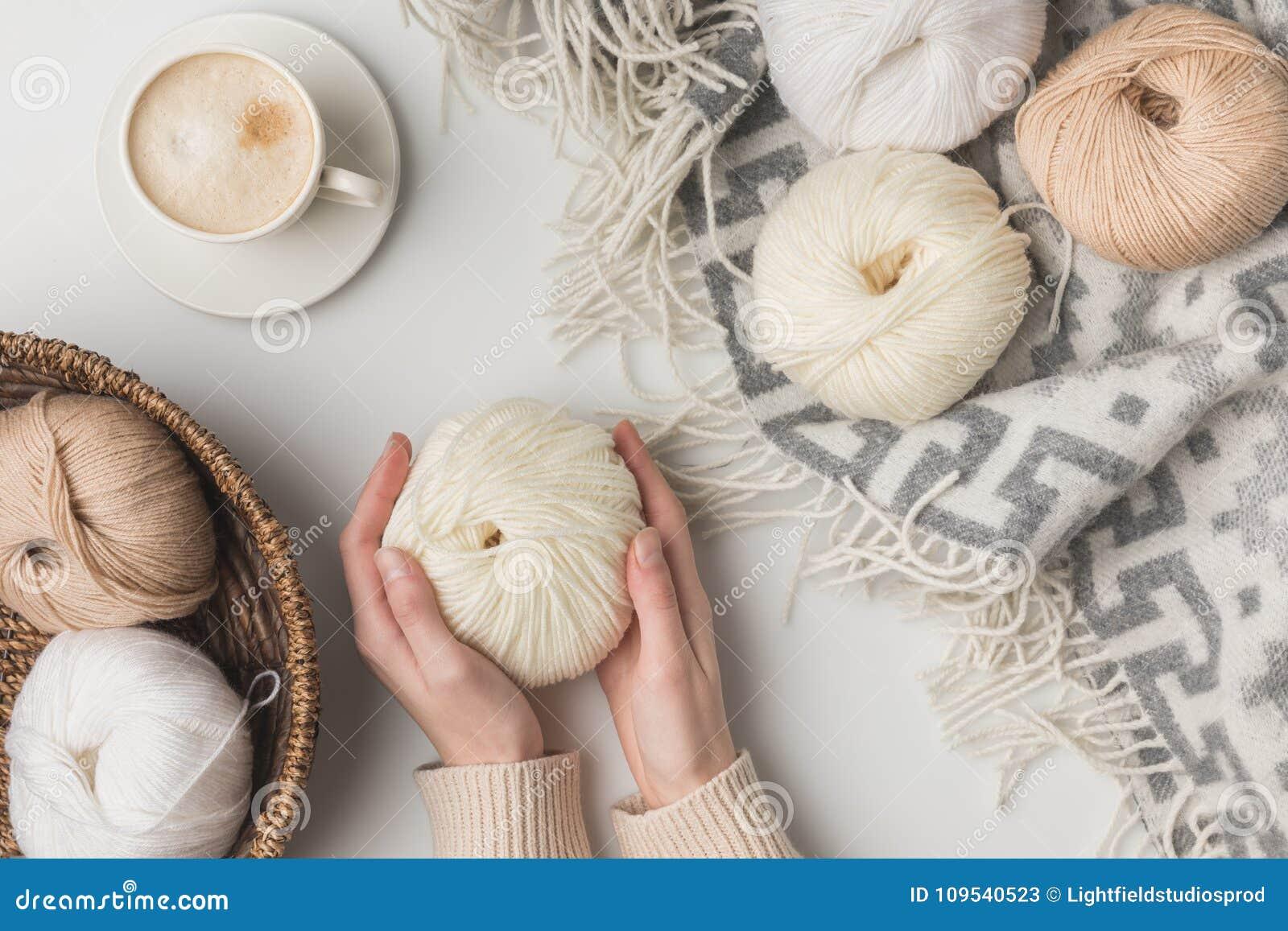 Bebouwde mening van de kop van de vrouwenholding koffie en garenballen op blaket en in mand