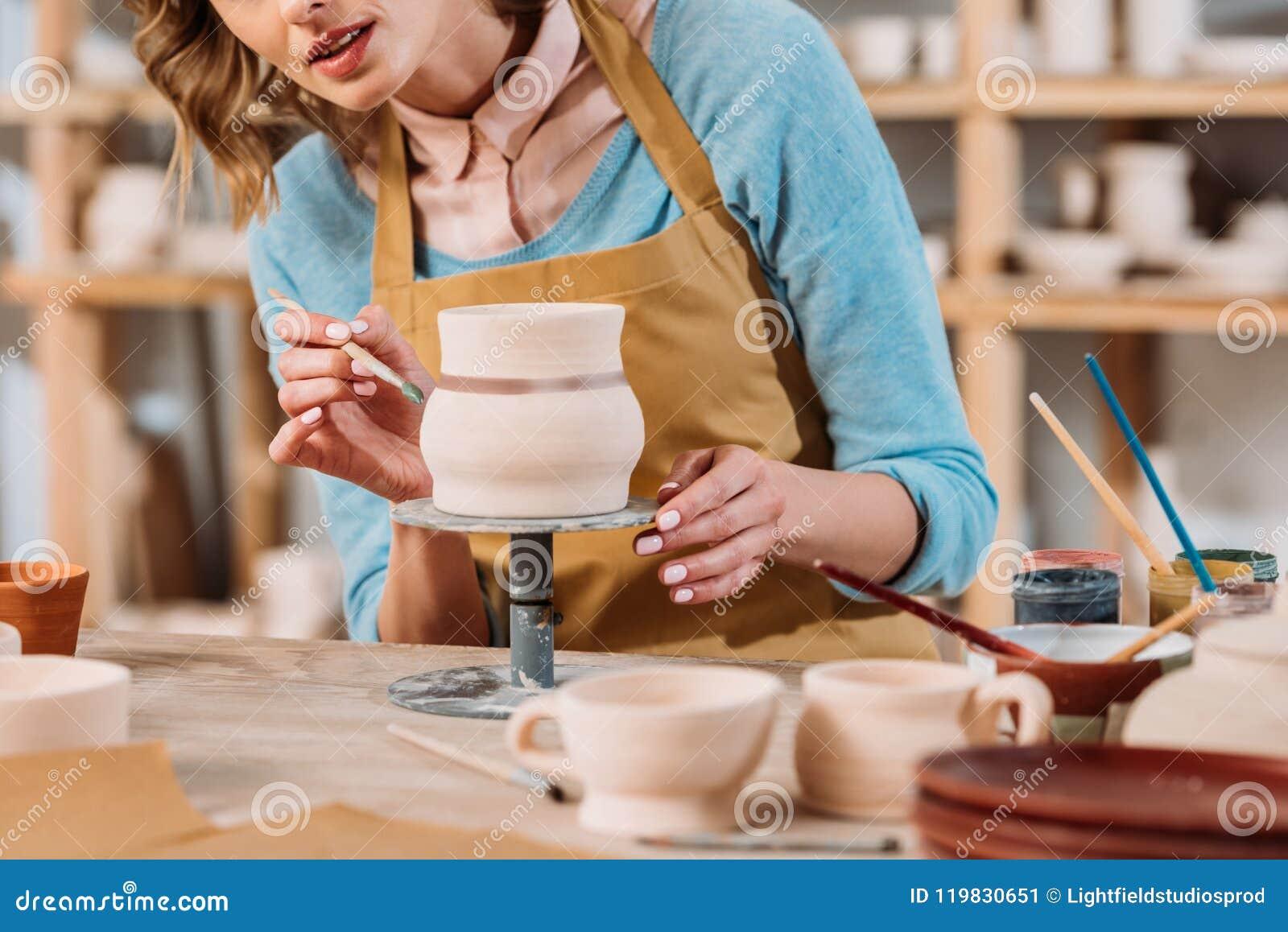 Bebouwde mening van vrouw die ceramische kruik schilderen
