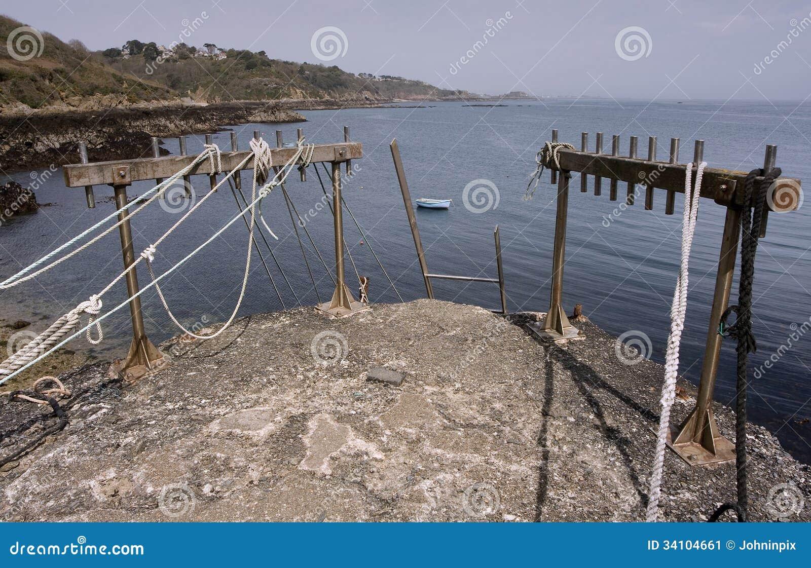 Bec du Nez, άκρη λιμενοβραχιόνων με τα σχοινιά και τη σκάλα πρόσδεσης, άποψη της ακτής, κόλπος Fermaine και οχυρό λιμένων Αγίου Pe