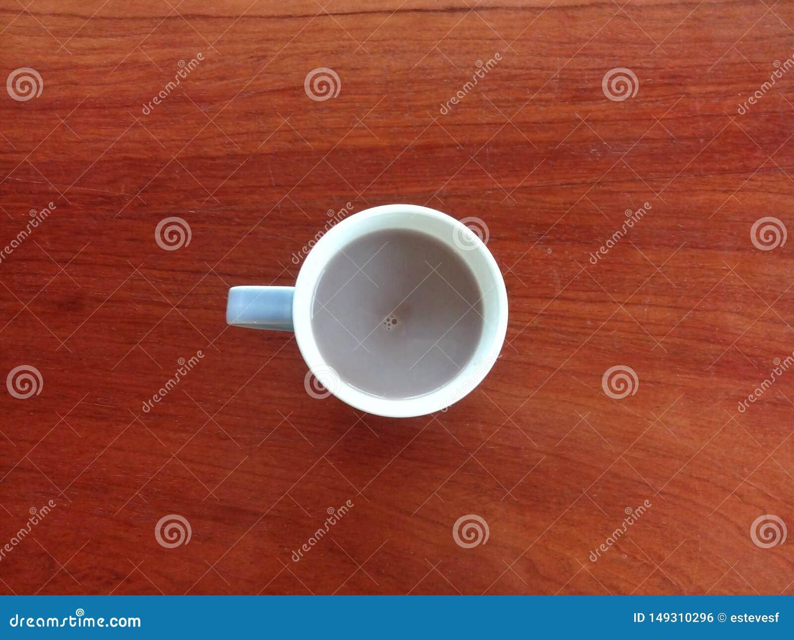 Becher dunkler Kakao auf der hölzernen Tabelle